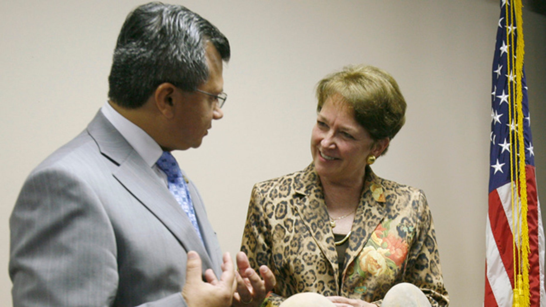 In this Sept. 23, 2008, file photo, U.S. ambassador to Ecuador Heather Hodges, right, speaks with Juan Carlos Toledo, consul general of the Ecuadorian consulate in Miami, by a display of pre-Columbian artifacts after a news conference at the Federal Bureau of Investigation Miami Field Office in North Miami Beach, Fla.