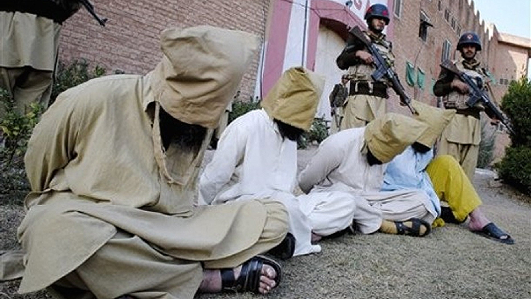 In this Dec. 19, 2010 file photo, Pakistani paramilitary soldiers stand guard next to hooded suspect militants captured during an operation in the Akakheil area, to show them to media in Bara, the main town of Pakistan's troubled tribal region Khyber along the Afghan border.