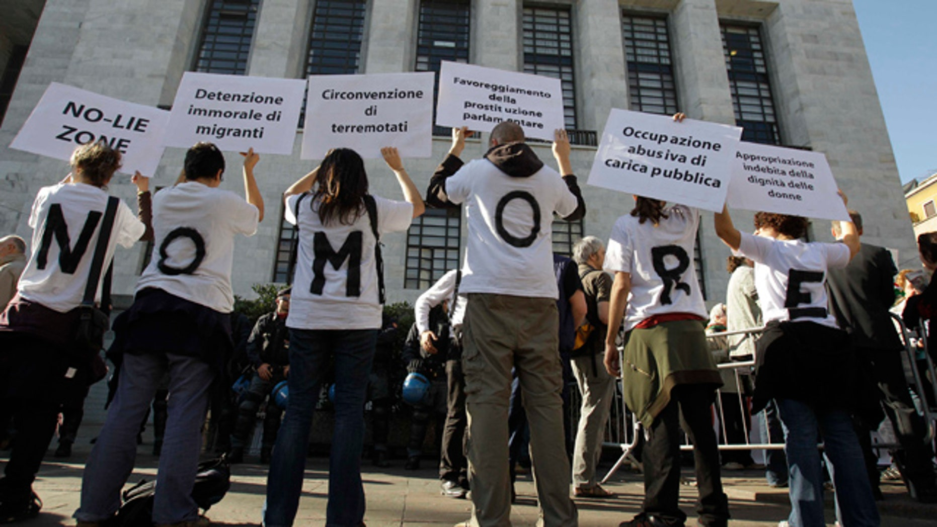 """April 6: People wear t-shirts composing the sentence """"No more"""" as they hold up placards during a protest outside the Milan court in Italy."""