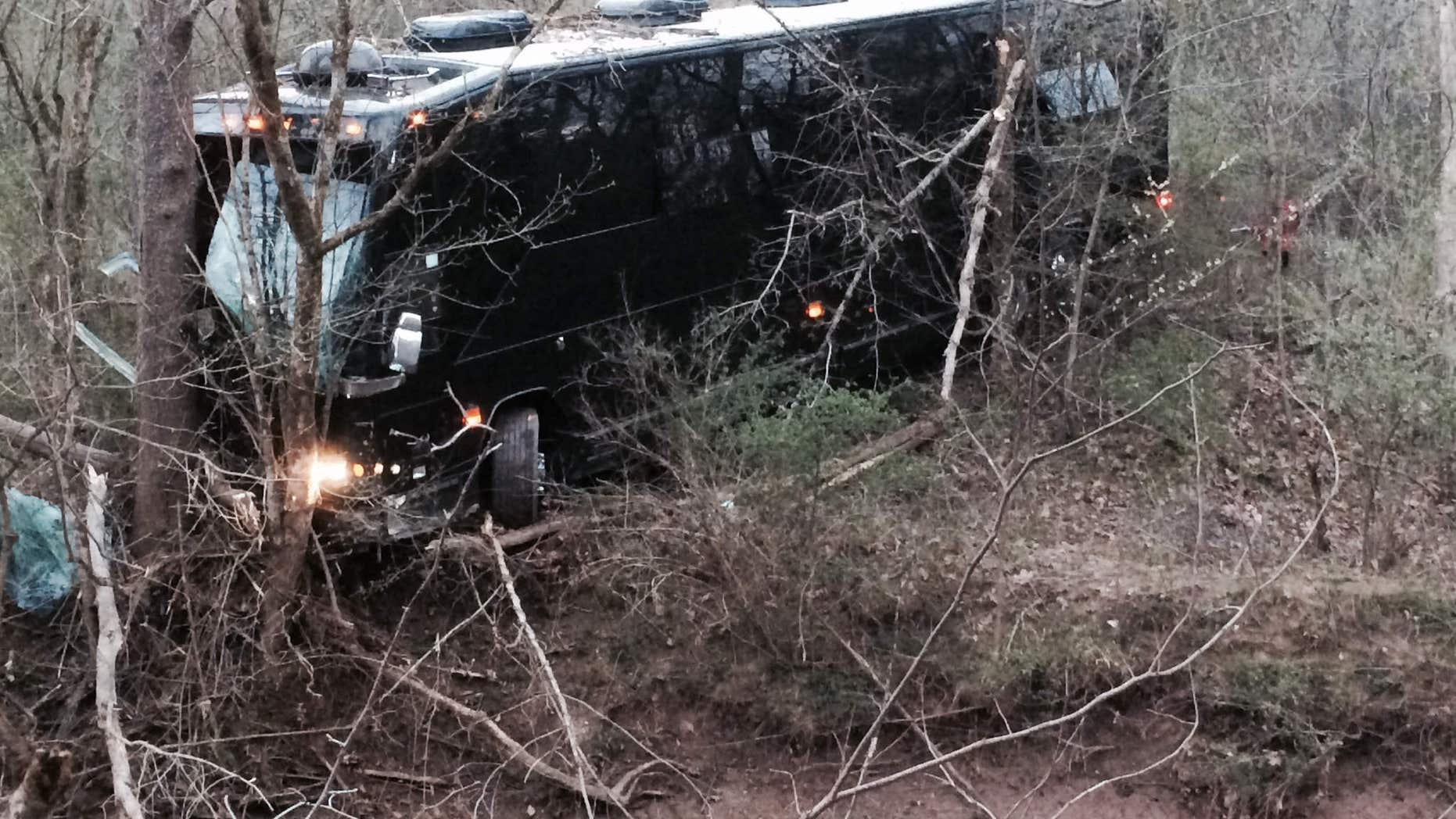 A tour bus for musician Gregg Allman's band rests against a tree near a creek after veering off Interstate 77 Wednesday morning, April 6, 2016, near Goldtown, W.Va.
