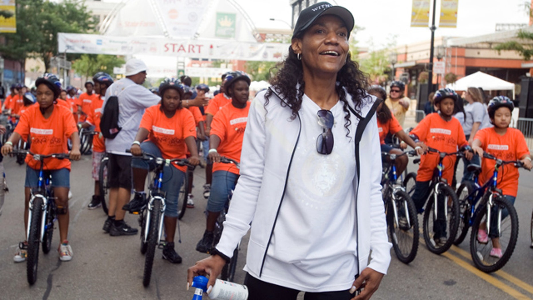"""This Aug. 22, 2009, file photo shows Gloria James, mother of basketball star LeBron James, watching a group of bike riders as she waits to start another group of riders at the """"King for Kids Bikeathon"""" in Akron, Ohio."""