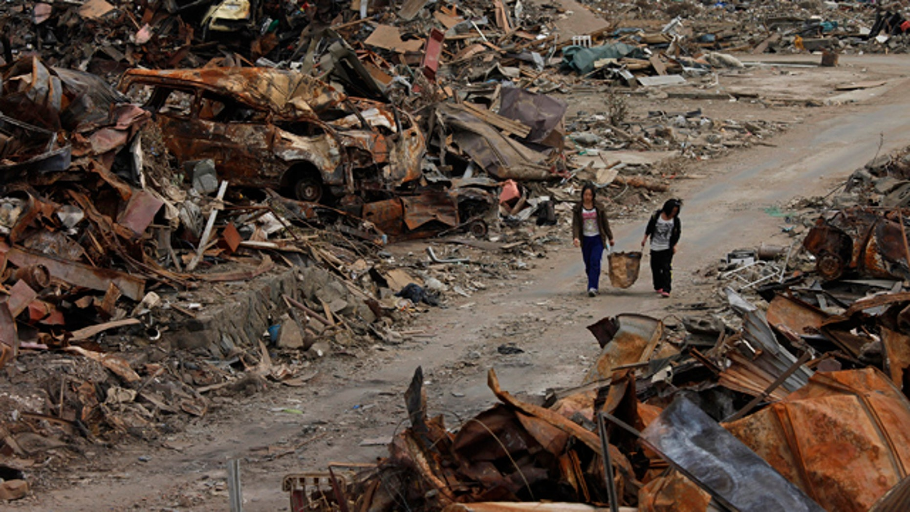 April 7: Two women walk past debris in an area devastated by the March 11 earthquake and tsunami in Ishinomaki, Miyagi Prefecture, northern Japan.