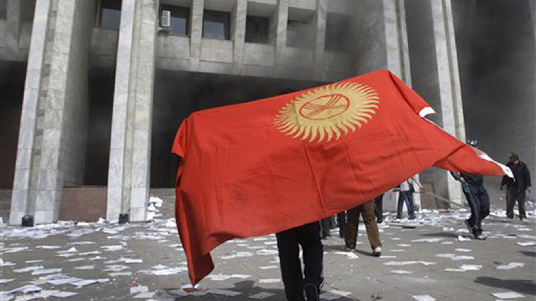 April 8: A protester covered by Kyrgyz national flag walks in front of Kyrgyz government headquarters on the central square in Bishkek.