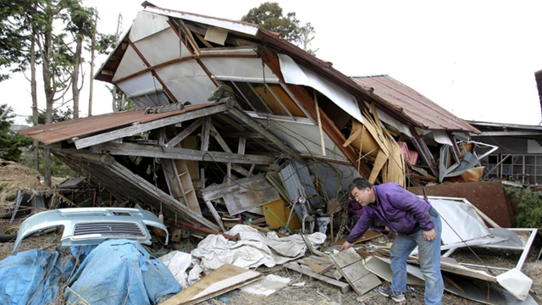 April 8: Takahiro Kato removes debris from his warehouse collapsed by Thursday night's strong aftershosk in Wakuya, Miyagi Prefecture, northeastern Japan.