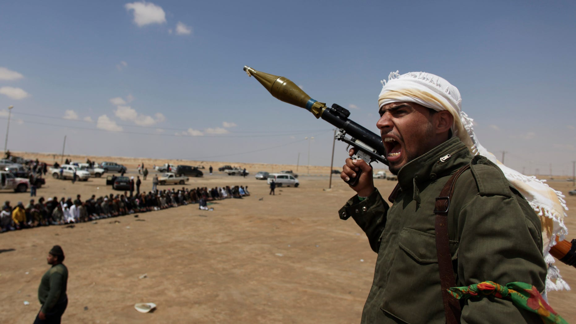 April 8: A Libyan rebel fighter, holding a rocket launcher, shouts religious slogans after gun shots were heard as fellow comrades offer prayers in the background in Ajdabia, Libya.