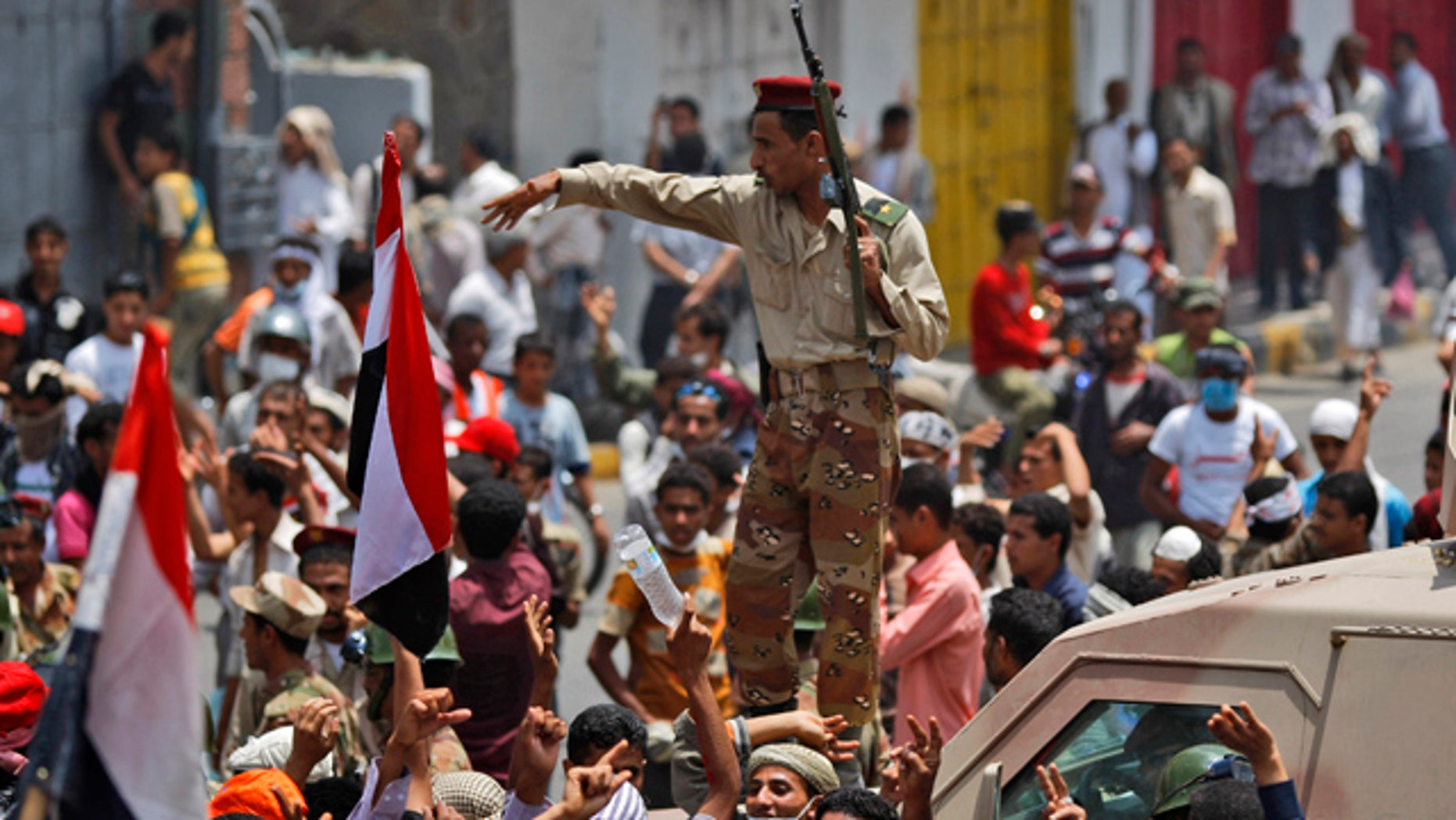 April 7: A Yemeni army officer gestures to anti-government protesters attending  a demonstration demanding the resignation of Yemeni President Ali Abdullah Saleh in Taiz, Yemen.