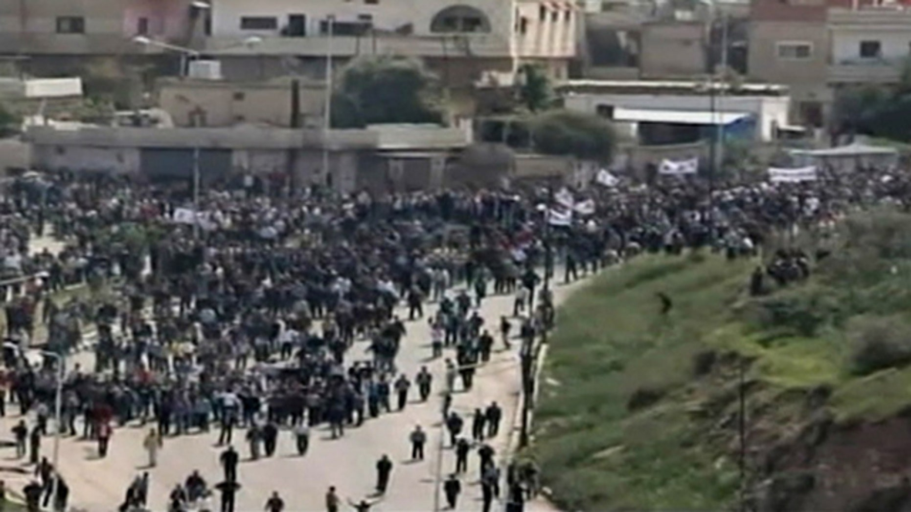 April 8: In this image made from television, demonstrators march in Daraa, Syria.