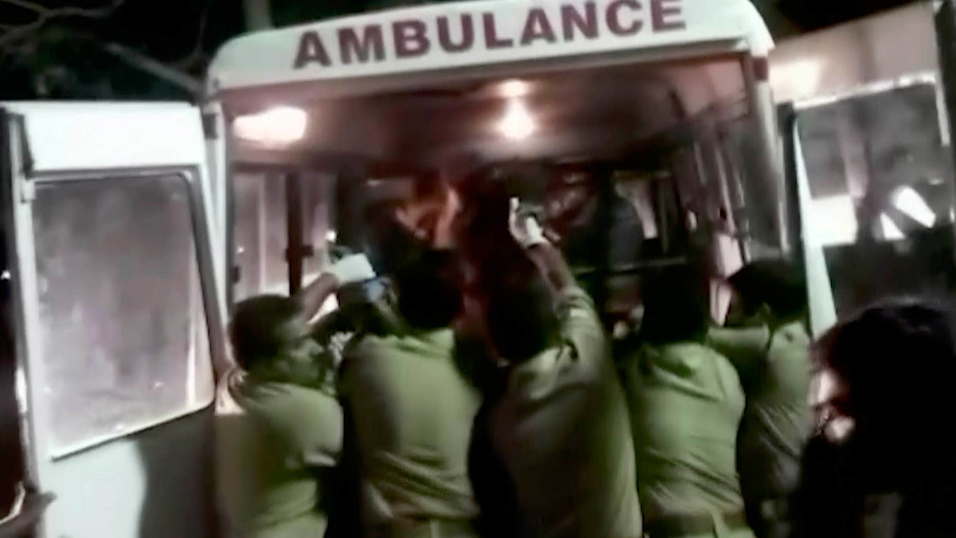 April 10, 2016: In this image made from video, officials put an injured person into an ambulance following a fire at a temple in Kollam, in the southern Indian state of Kerala.