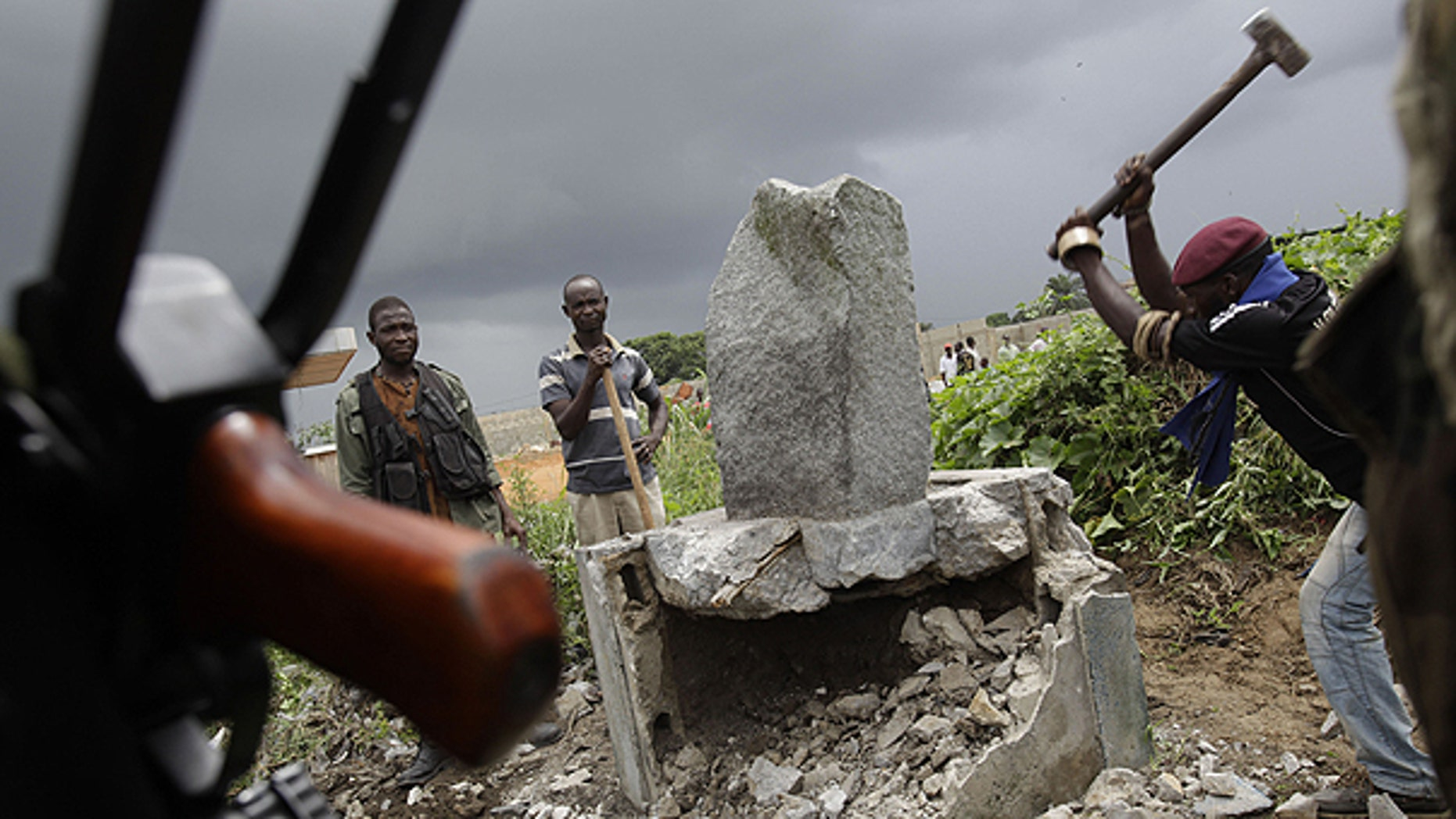 April 10: A soldier allied with Alassane Ouattara knocks down a monument believed to mystically provide strength and support to Laurent Gbagbo, in the Youpougon neighborhood of Abidjan, Ivory Coast.