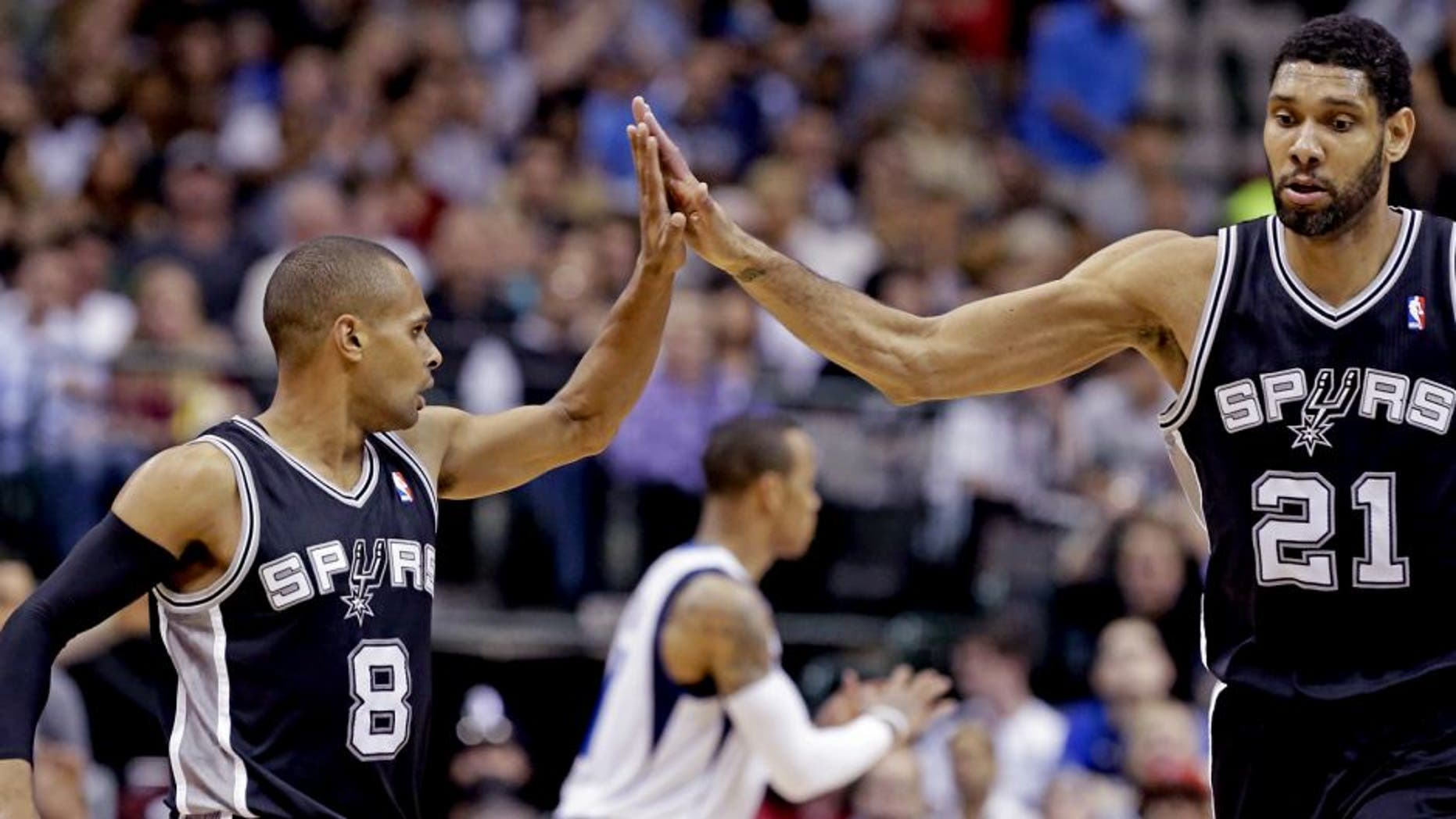 San Antonio Spurs guard Patty Mills (8) receives congratulations from Tim Duncan (21) during the second half an NBA basketball game against the Dallas Mavericks on Thursday, April 10, 2014, in Dallas. The Spurs won 109-100. (AP Photo/LM Otero)