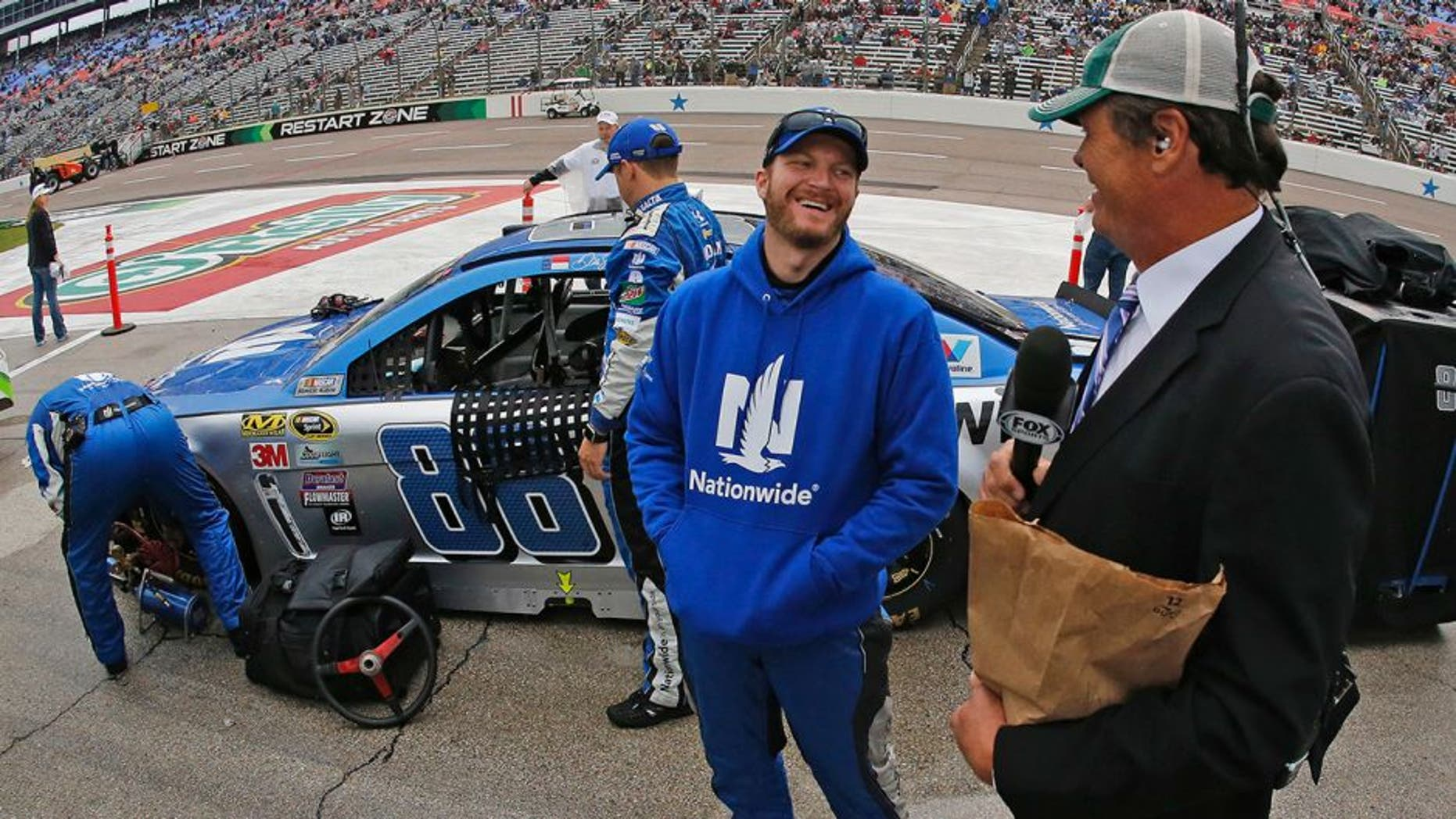 Sprint Cup Series driver Dale Earnhardt Jr. (88) with broadcaster Michael Waltrip on a rain-soaked pit row before the Duck Commander 500 on Saturday, April 9, 2016, at Texas Motor Speedway in Fort Worth, Texas. (Paul Moseley/Fort Worth Star-Telegram/TNS via Getty Images)