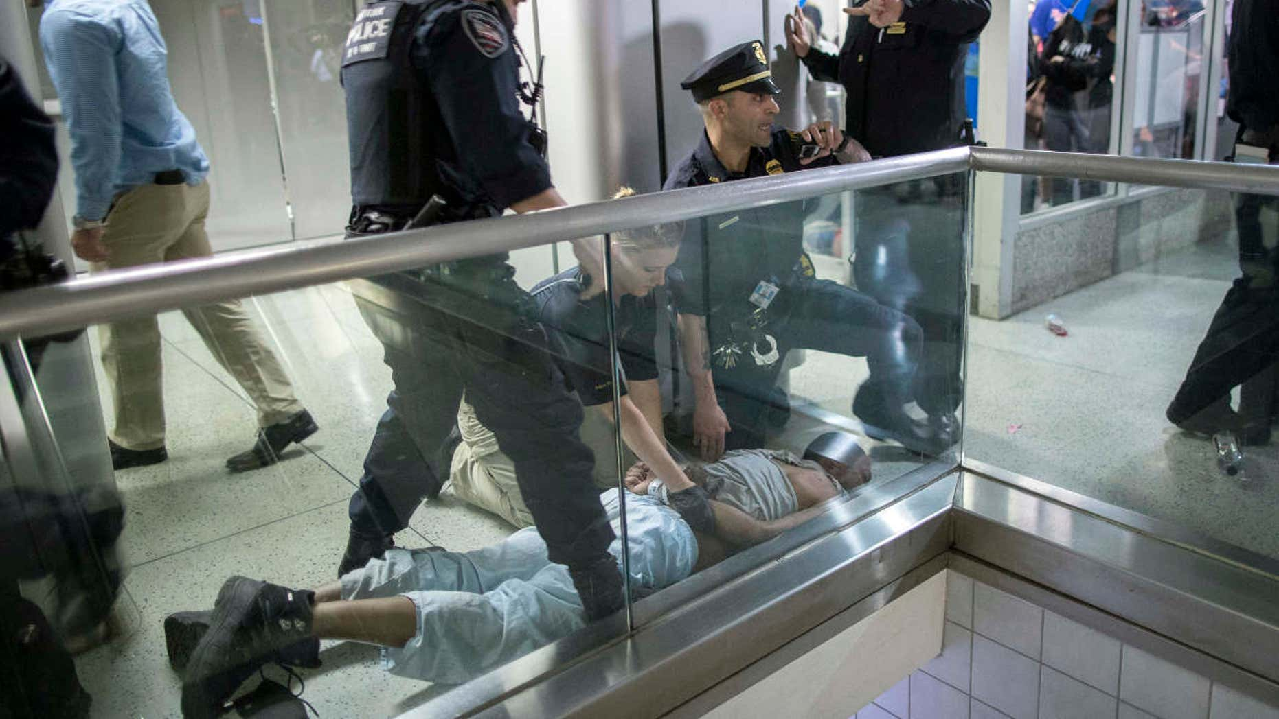 New York City police officers detain a passenger from a disabled New Jersey Transit train who became belligerent and sparked a stampede among passengers leaving the overcrowded station once the train finally arrived at New York's Penn Station, Friday, April 14, 2017.
