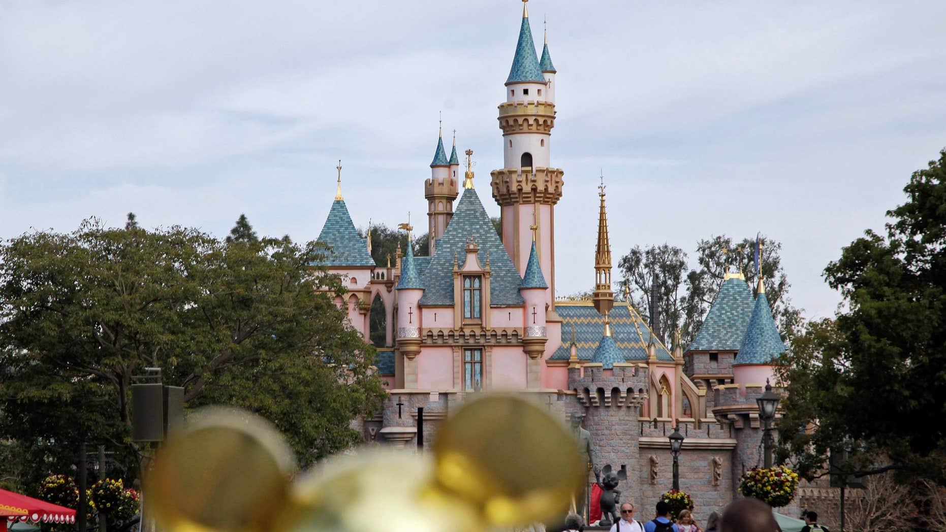 Jan. 22, 2015: In this file photo, people walk toward Sleeping Beauty's Castle at Disneyland in Anaheim, Calif.
