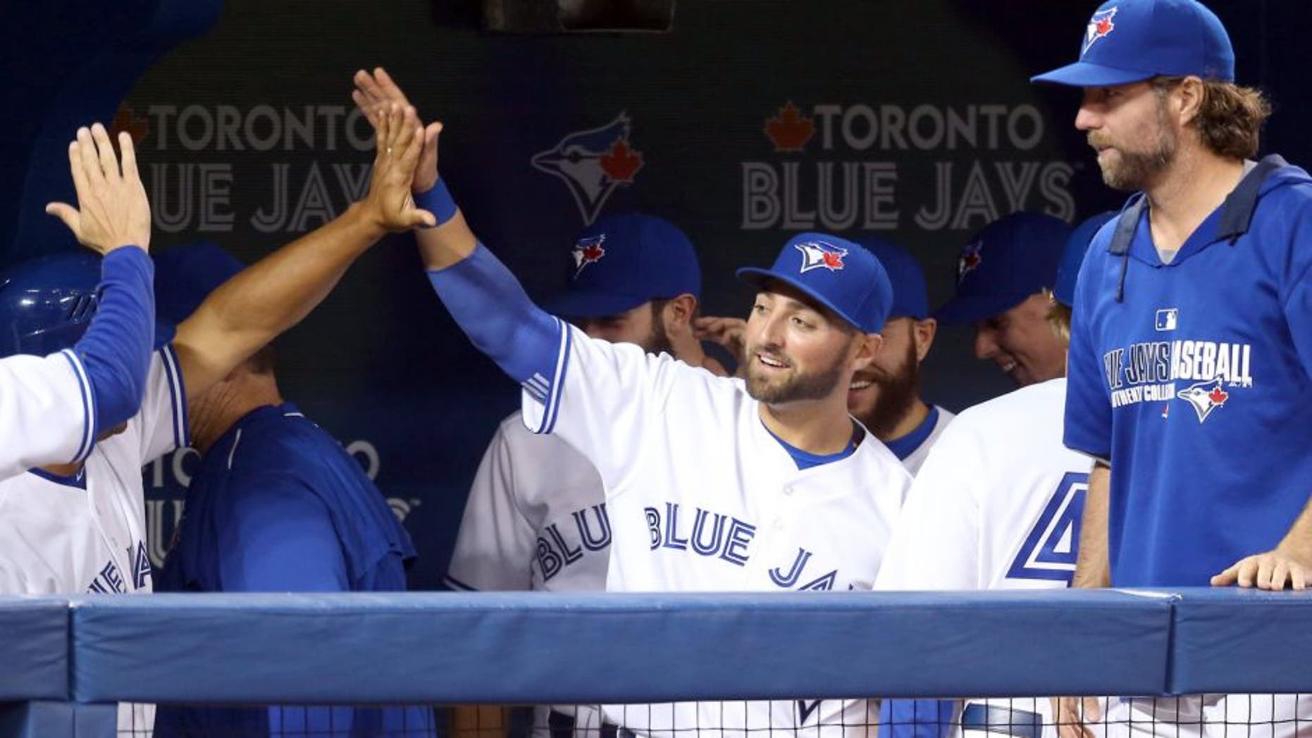 TORONTO, CANADA - APRIL 15: Kevin Pillar #11 of the Toronto Blue Jays is congratulated by teammates after making a leaping catch in the seventh inning during an MLB game against the Tampa Bay Rays on April 15, 2015 at Rogers Centre in Toronto, Ontario, Canada. All uniformed team members are wearing jersey number 42 in honor of Jackie Robinson Day. (Photo by Tom Szczerbowski/Getty Images)