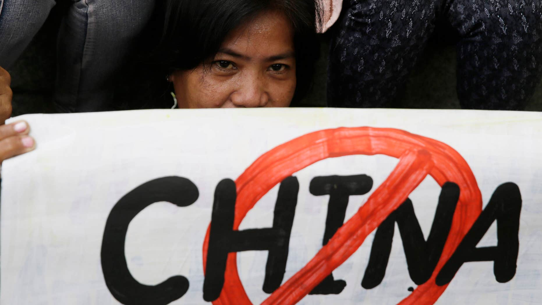 April 17, 2015: A protester displays a placard during a rally at the Chinese Consulate at the financial district of Makati city, east of Manila, Philippines.