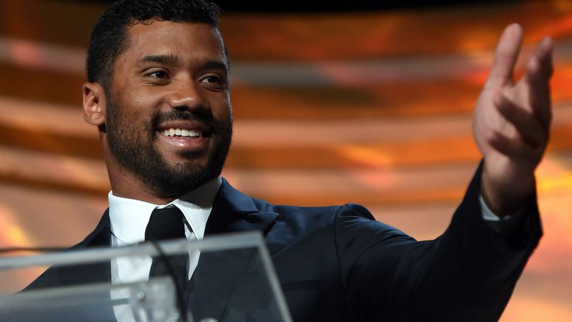 PHOENIX, AZ - MARCH 28: Seattle Seahawks quarterback Russell Wilson accepts an award during Muhammad Ali's Celebrity Fight Night XXI at the JW Marriott Phoenix Desert Ridge Resort & Spa on March 28, 2015 in Phoenix, Arizona. (Photo by Ethan Miller/Getty Images for Celebrity Fight Night)