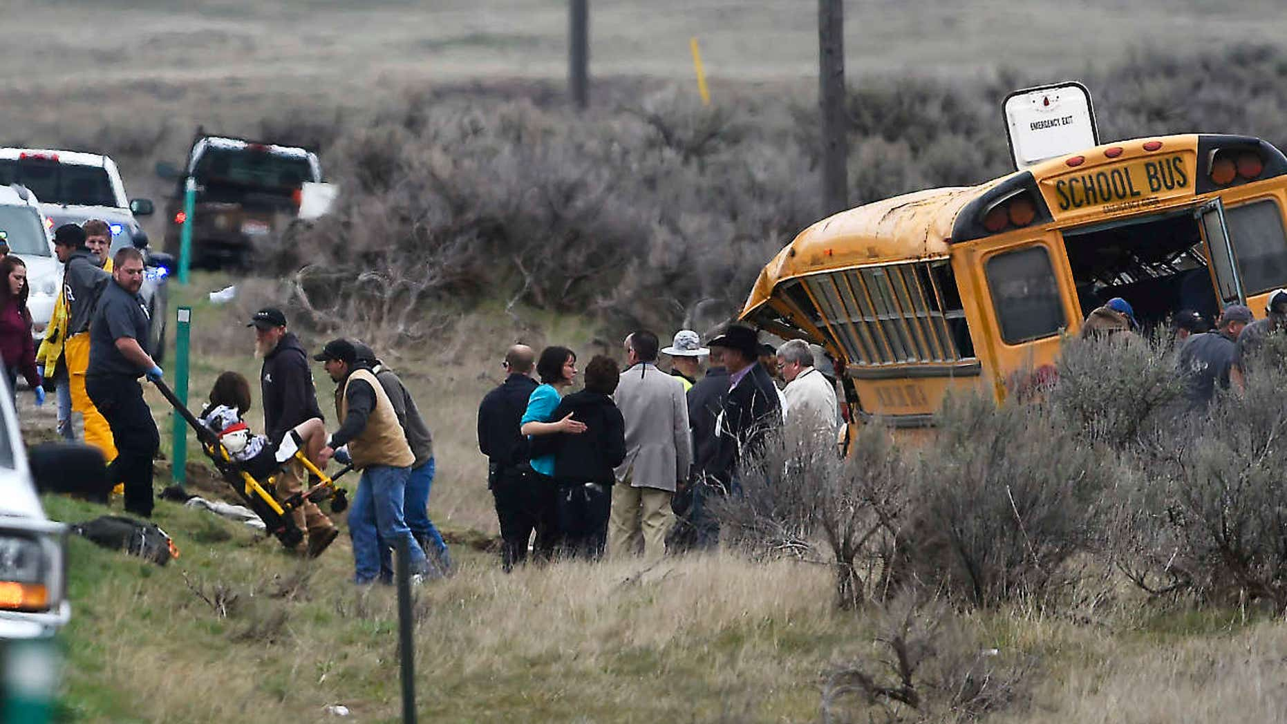 Emergency personnel help to remove passengers after school bus that Tuesday, April 18, 2017, west of Richfield, Idaho.