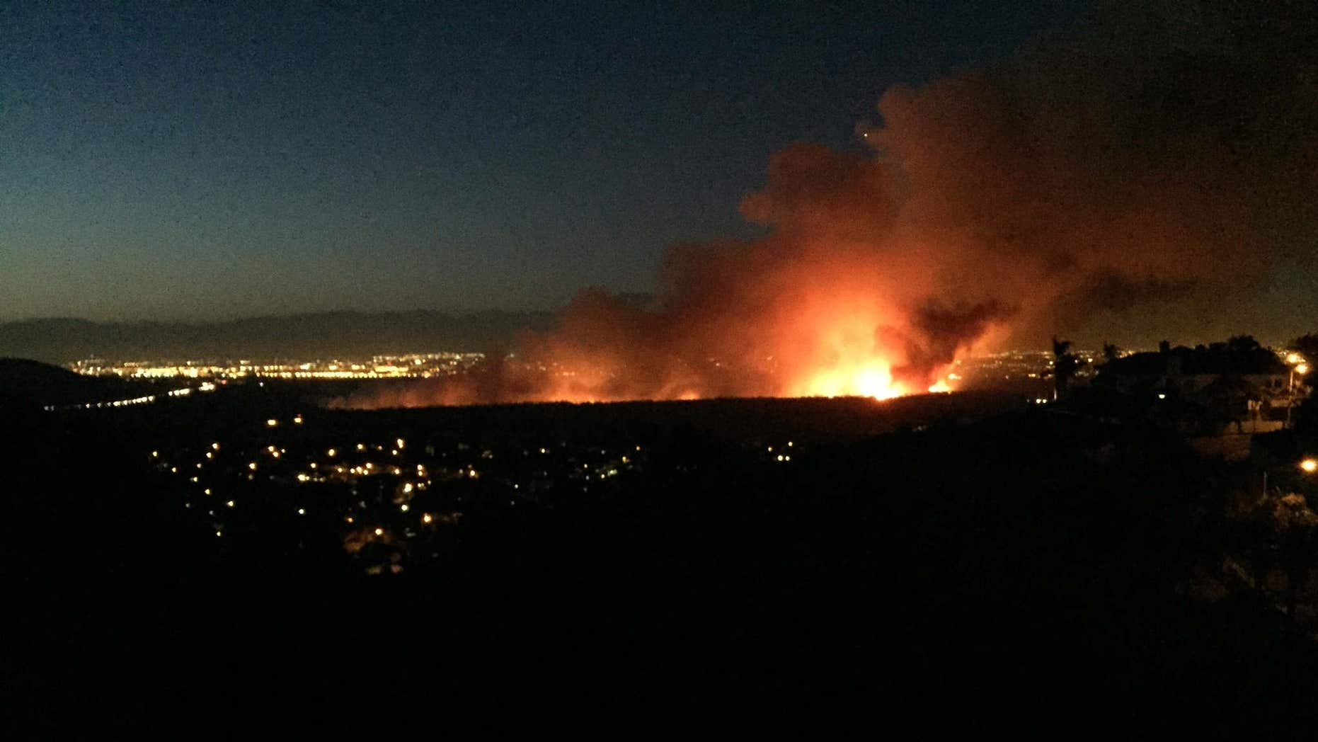 April 18, 2015: A brush fire burns in the Dam Prado Dam Flood Control Basin north of the city of Corona, Calif.