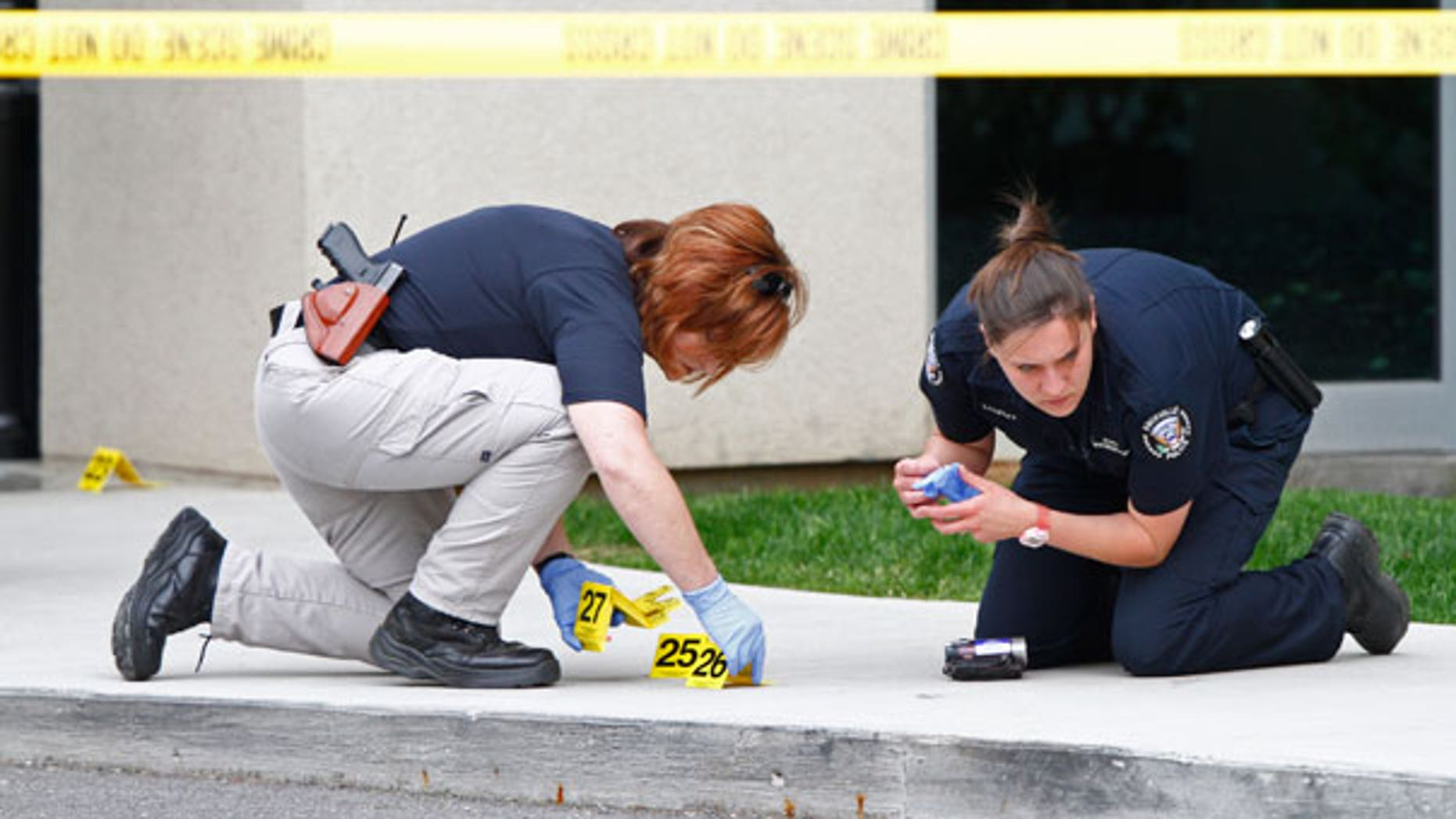 April 19: Police work the scene where a gunman opened fire outside Parkwest Medical Center in Knoxville, Tenn., killing a woman and injuring two others before committing suicide.