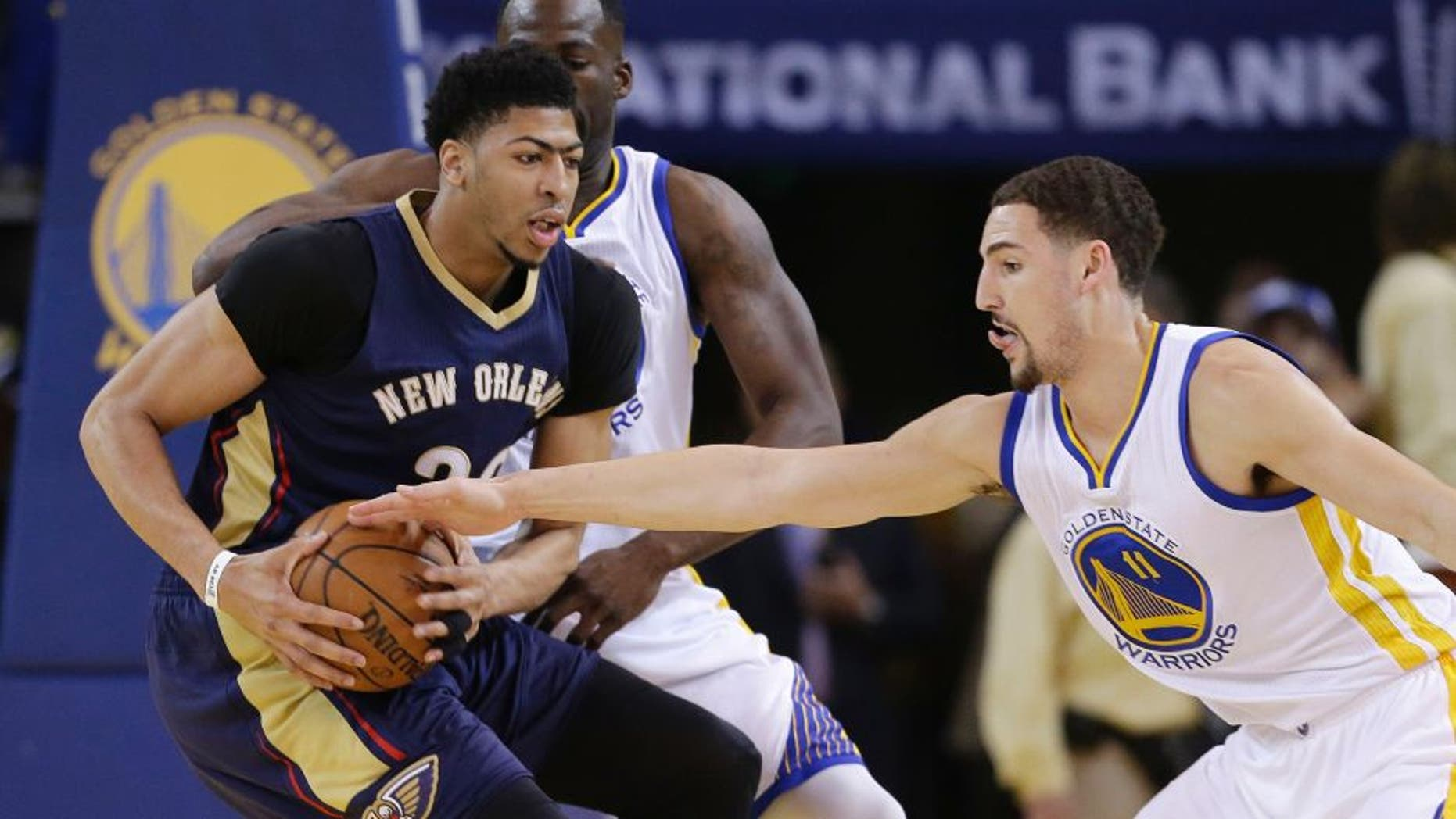 Golden State Warriors' Klay Thompson (11) defends on New Orleans Pelicans' Anthony Davis during the first half in Game 2 of a first-round NBA basketball playoff series Monday, April 20, 2015, in Oakland, Calif. (AP Photo/Marcio Jose Sanchez)