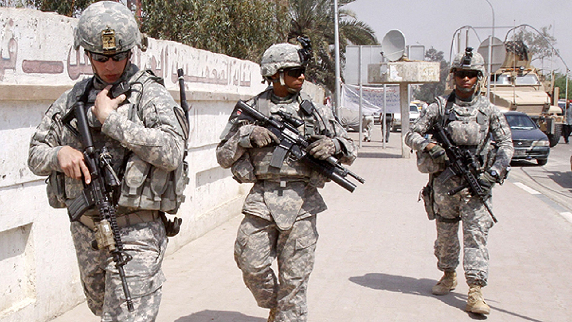 March 23: U.S. troops stand guard outside a local journalists' union office in Basra, Iraq. As the U.S. tries to move from invading power to normal diplomatic partner and the last American troops obligated to be gone by year's end, the protection of American diplomats will fall almost entirely to private contractors and Iraqi security forces.