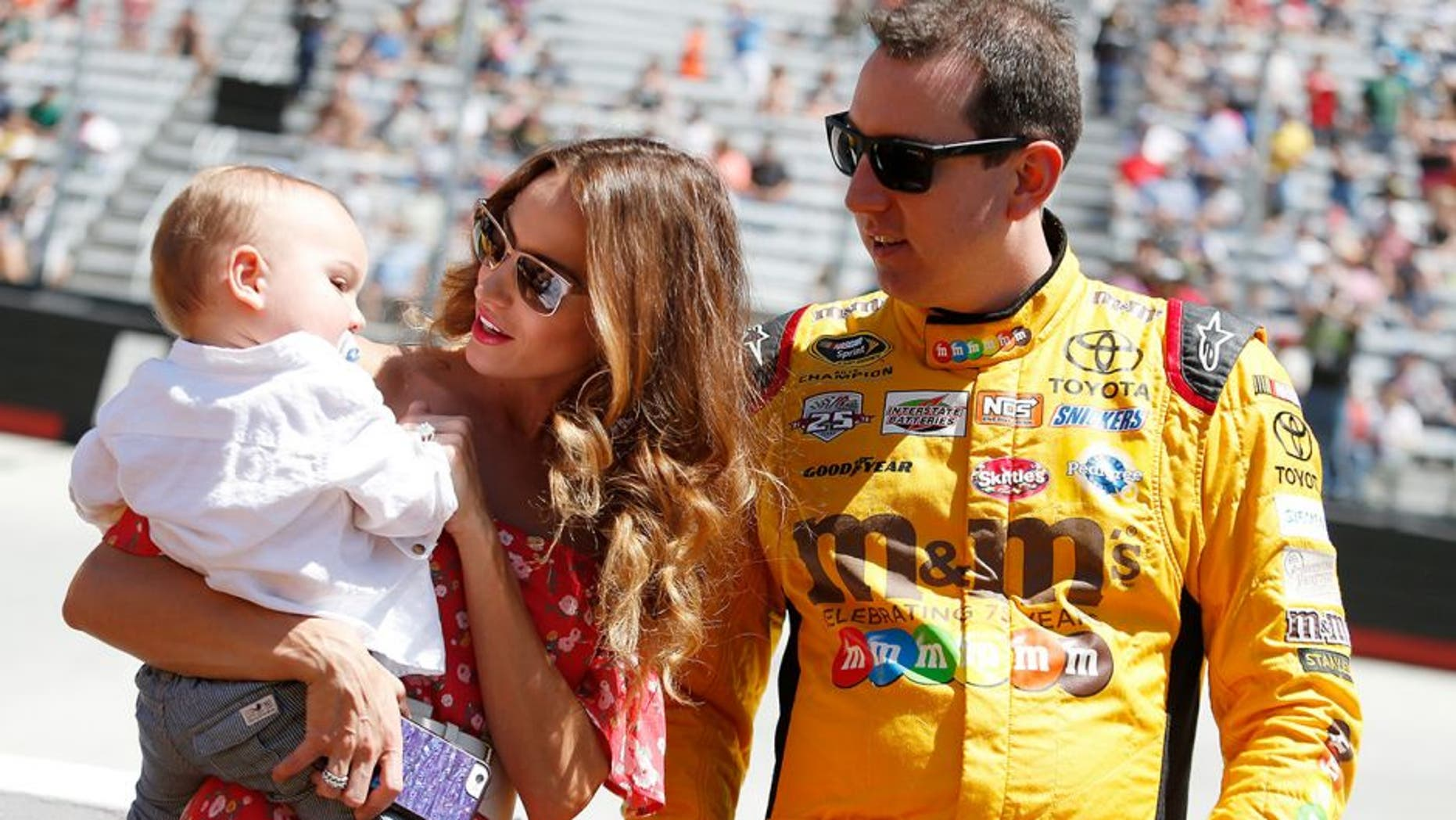 BRISTOL, TN - APRIL 17: Kyle Busch, driver of the #18 M&M's Toyota, stands on the grid with wife Samantha Busch and son Brexton prior to the NASCAR Sprint Cup Series Food City 500 at Bristol Motor Speedway on April 17, 2016 in Bristol, Tennessee. (Photo by Matt Hazlett/Getty Images)