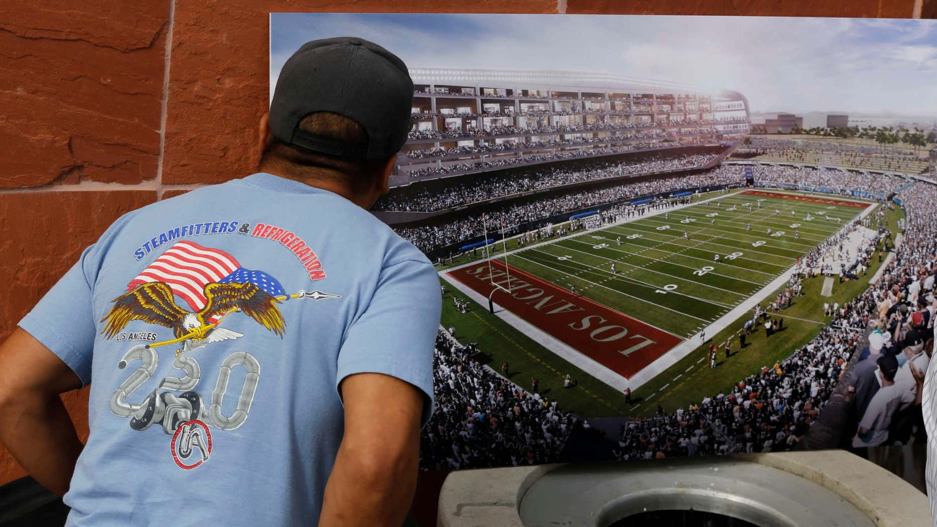 Feb. 19, 2015: A football fan checks a rendering for a proposed NFL football stadium by the owners of the San Diego Chargers and Oakland Raiders during a news conference in Carson, Calif.