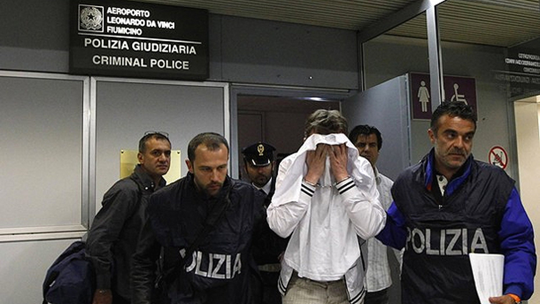 April 25: A man (in white) from Kazakhstan is escorted by police as he leaves Fiumicino airport, northeast Rome. The man, using a knife, tried to hijack an Alitalia flight from Paris to Rome on Sunday night, demanding it be flown to Libya, but was quickly overpowered and arrested when the plane landed, officials and witnesses said.