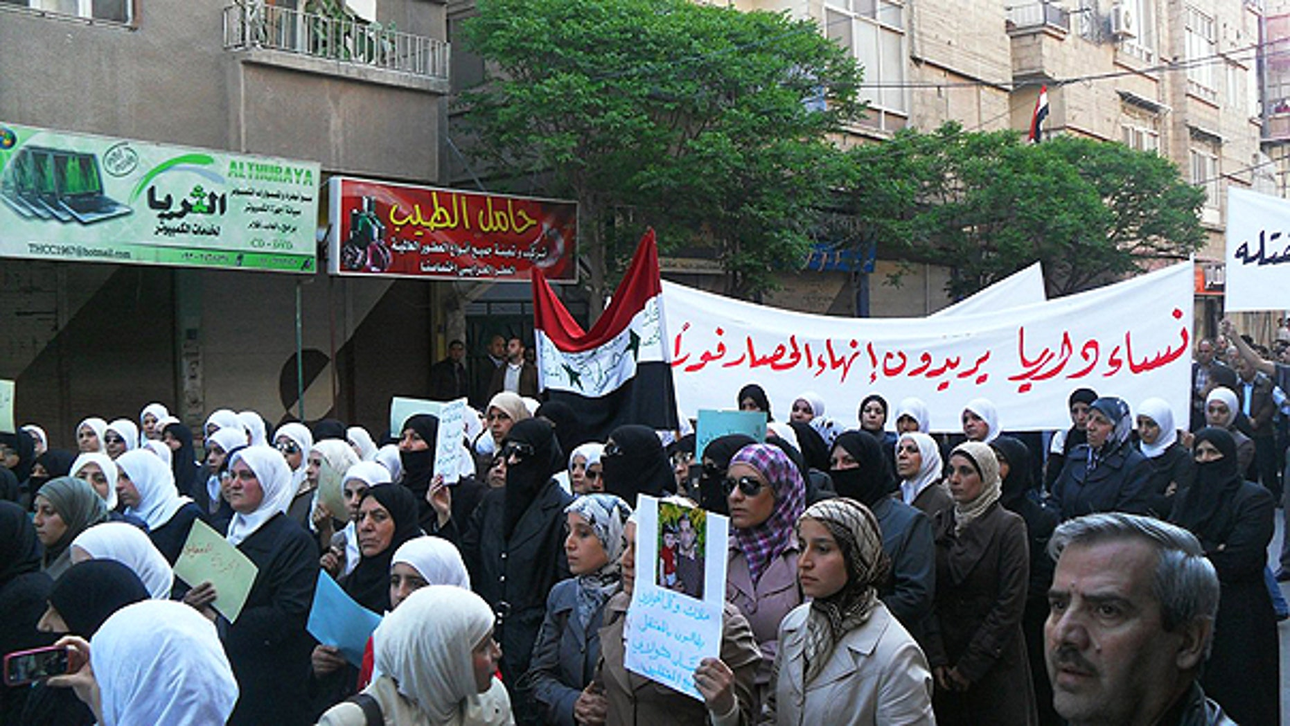 April 25: In this citizen journalism image made on a mobile phone and acquired by the Associated Press, Syrian women carry a banner in Arabic that reads: 'the women of Daraya want an end to the siege,' as they protest in Daraya, southwest of Damascus, Syria.