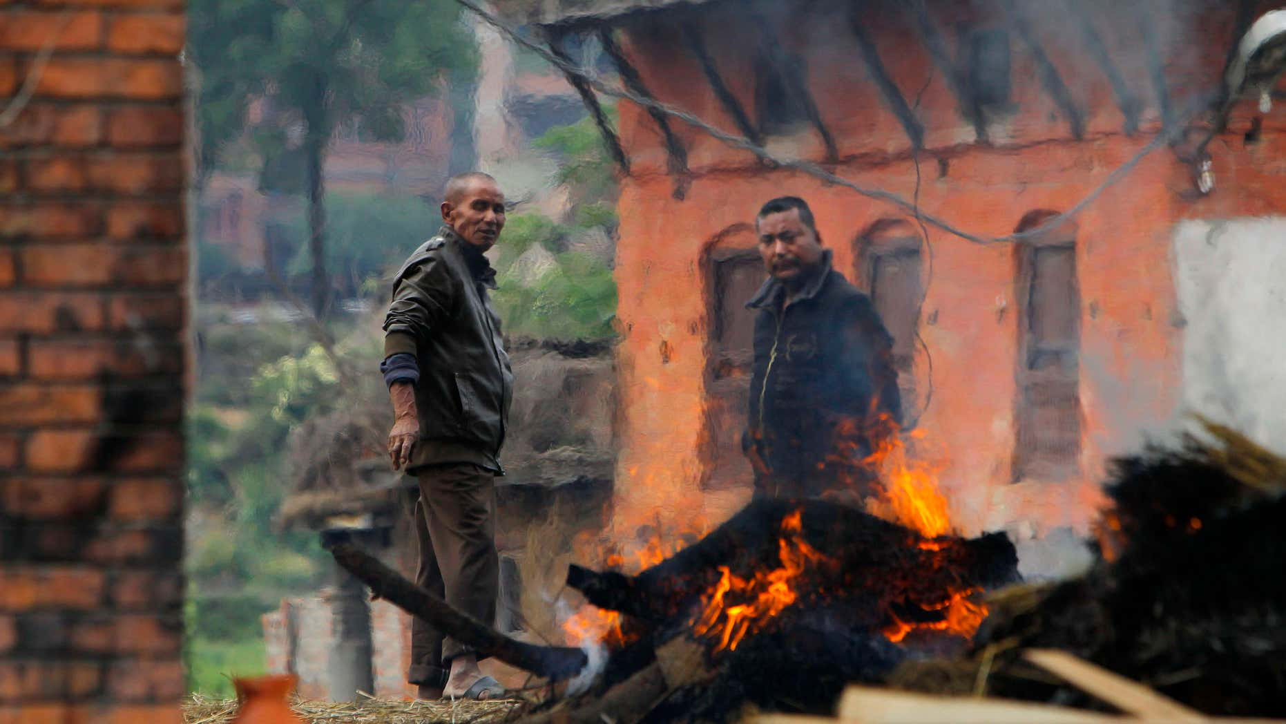 April 26, 2015: Nepalese people stand beside the funeral pyre of a family member who died in Saturday's earthquake in Bhaktapur, Nepal.