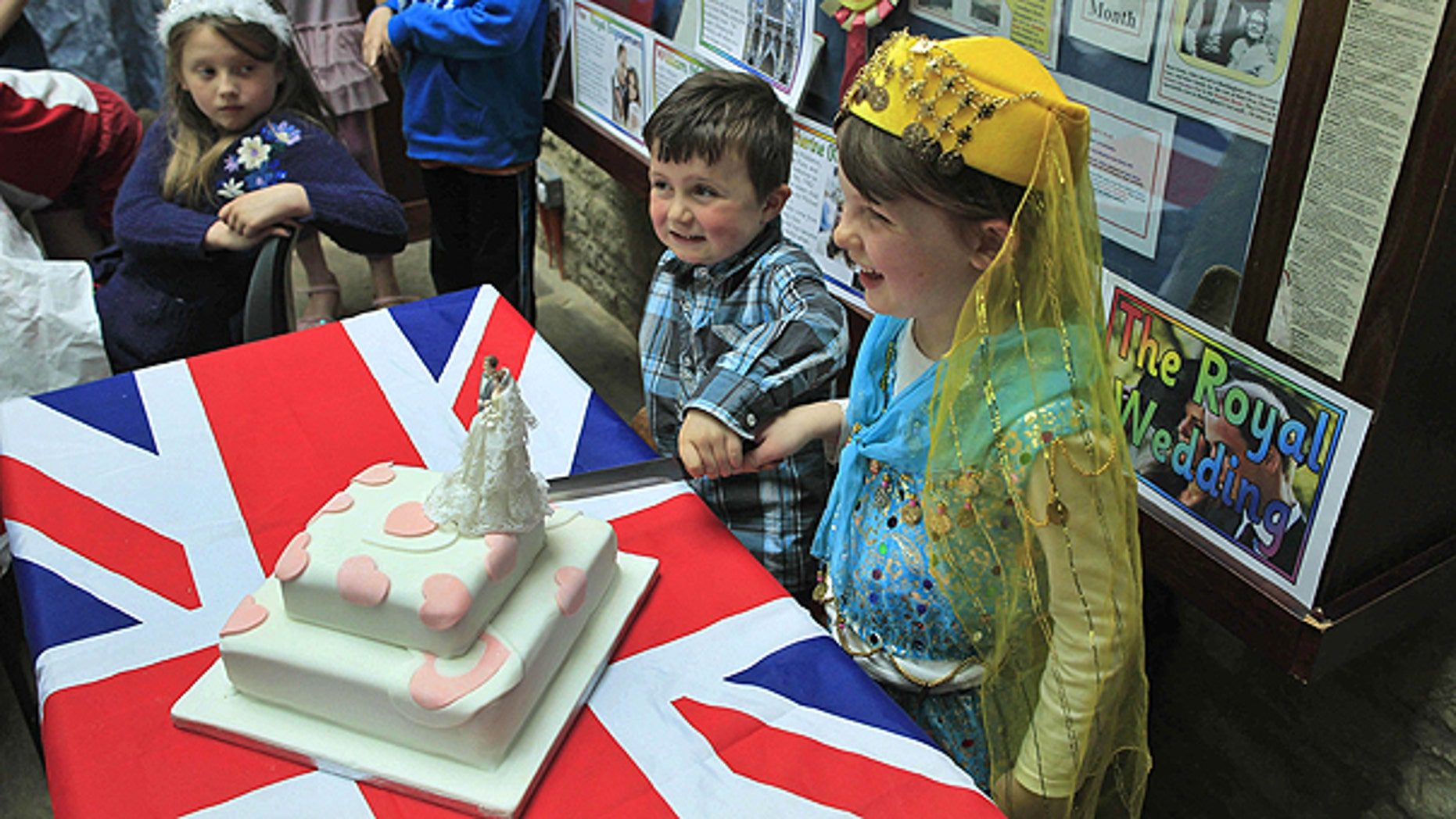 April 26: Local children Gabriel Perry, second right, aged four, and Caitlin Argles-Clarke, right, aged five, pose for photographs to cut the wedding cake after winning the best costumes awards during a 'street' party to mark the royal wedding in the town of Buckingham, England.