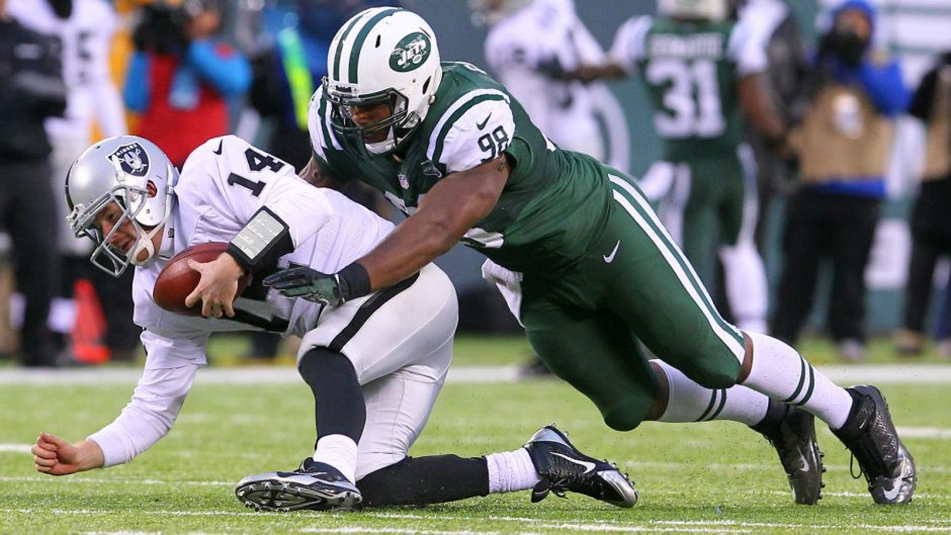 Dec 8, 2013; East Rutherford, NJ, USA; Oakland Raiders quarterback Matt McGloin (14) recovers his own fumble while being tackled by New York Jets defensive end Quinton Coples (98) during the second half at MetLife Stadium. The Jets defeated the Raiders 37-27. Mandatory Credit: Ed Mulholland-USA TODAY Sports