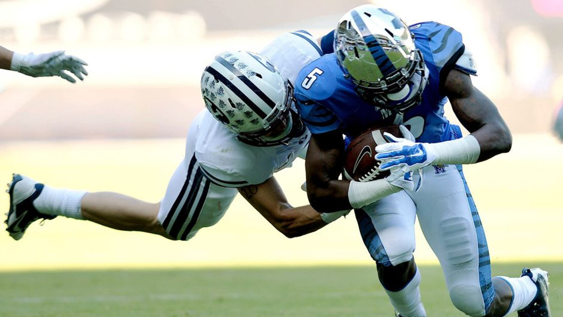 Dec 22, 2014; Miami, FL, USA; Memphis Tigers wide receiver Mose Frazier (5) is tackled by Brigham Young Cougars linebacker Alani Fua (5) during the first quarter in the Miami Beach Bowl at Marlins Park. Mandatory Credit: Steve Mitchell-USA TODAY Sports