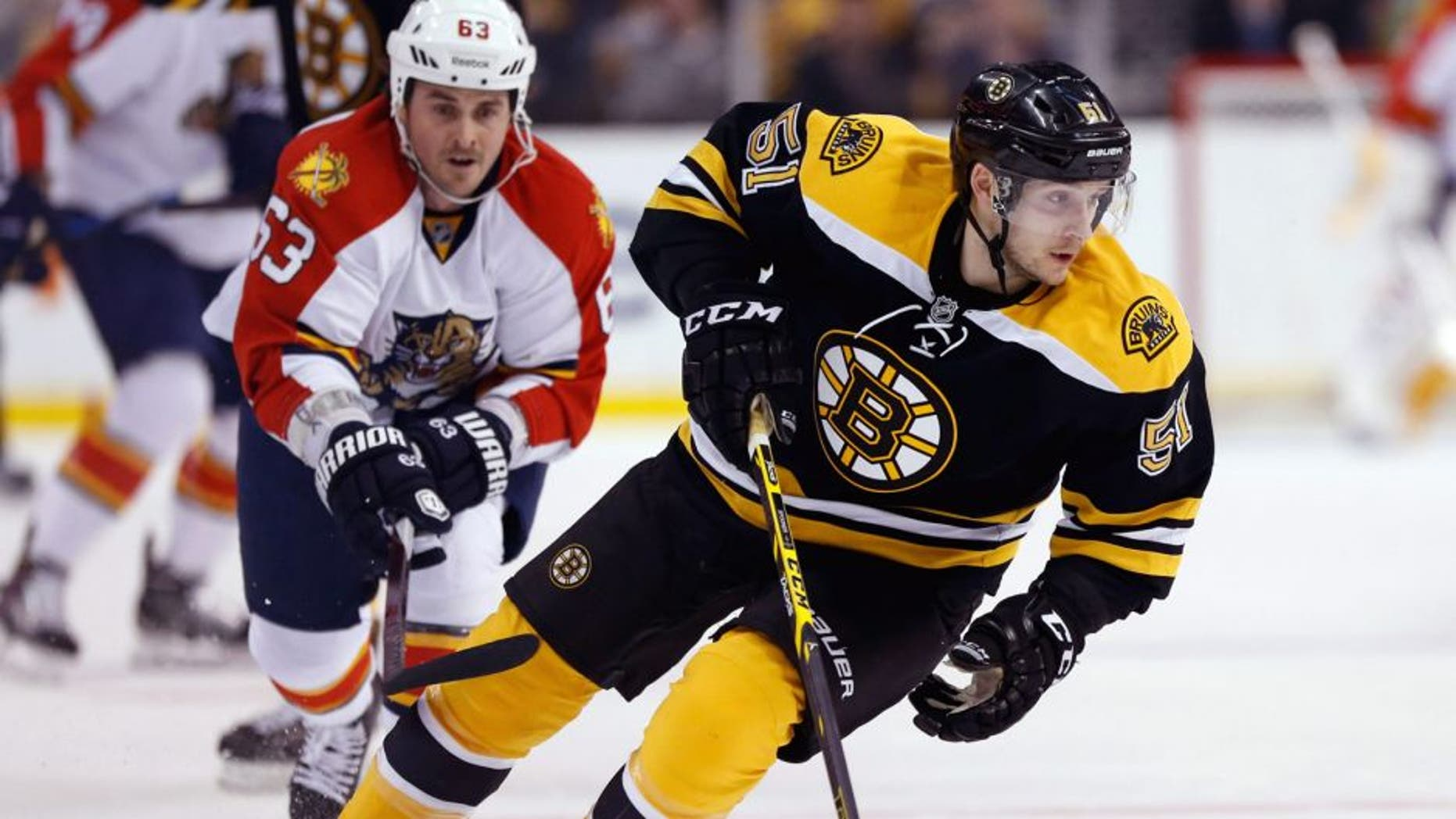 Mar 31, 2015; Boston, MA, USA; Boston Bruins center Ryan Spooner (51) keeps the puck away from Florida Panthers center Dave Bolland (63) during the first period at TD Banknorth Garden. Mandatory Credit: Greg M. Cooper-USA TODAY Sports