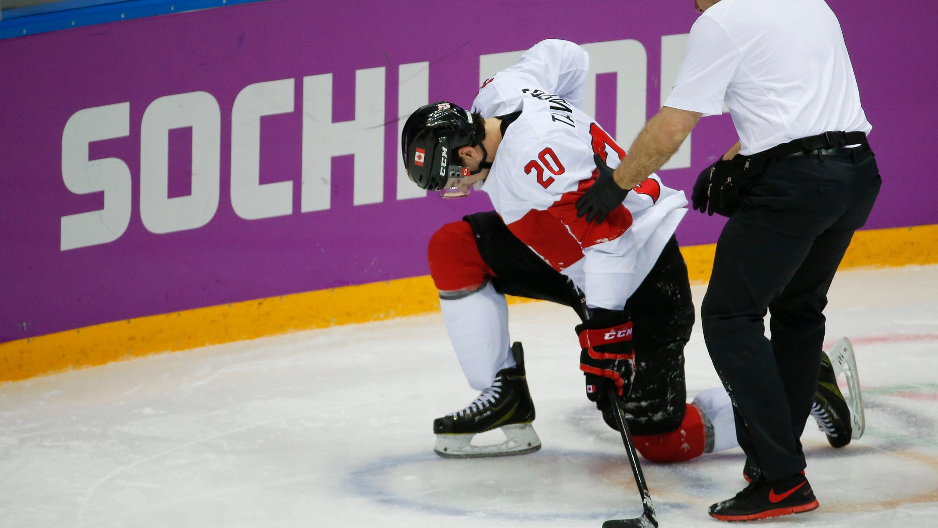 Canada forward John Tavares is helped up off the ice by a trainer during the second period of a men's quarterfinal ice hockey game against Latvia at the 2014 Winter Olympics, Wednesday, Feb. 19, 2014, in Sochi, Russia. Tavares is out for the rest of the Olympics with an unspecified leg injury. (AP Photo/Mark Humphrey)