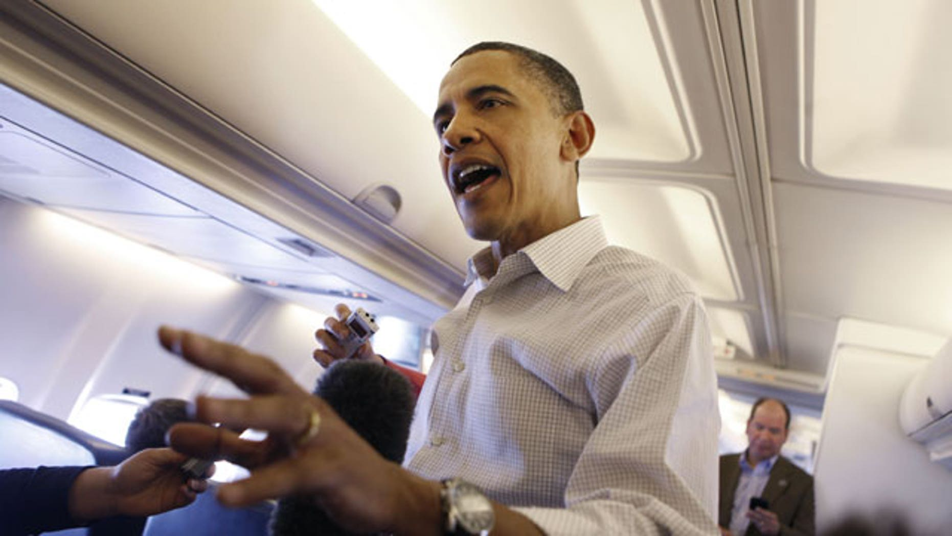 April 28: President Barack Obama answers question for members of the media aboard Air Force One entroute to Andrews Air Force Base.