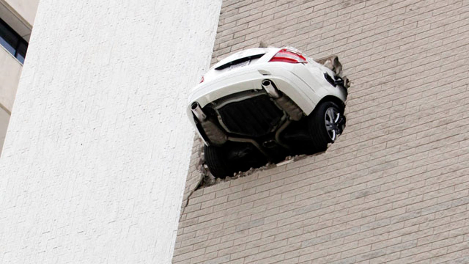April 28: No injuries were reported when the car seen here went through the 6th floor wall of a parking garage in Tulsa, Okla.