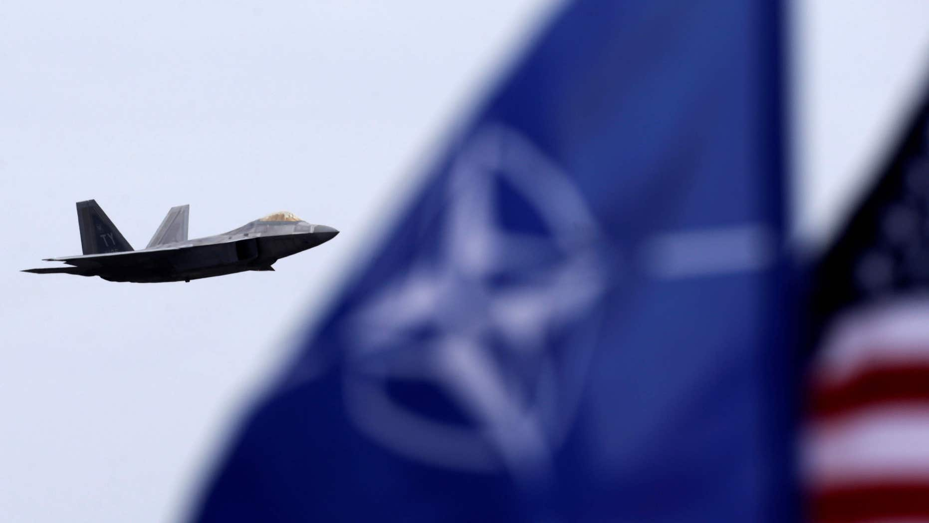 April 27, 2016: NATO and U.S. flags flutter as U.S. Air Force F-22 Raptor fighter flies over the military air base in Siauliai, Lithuania.