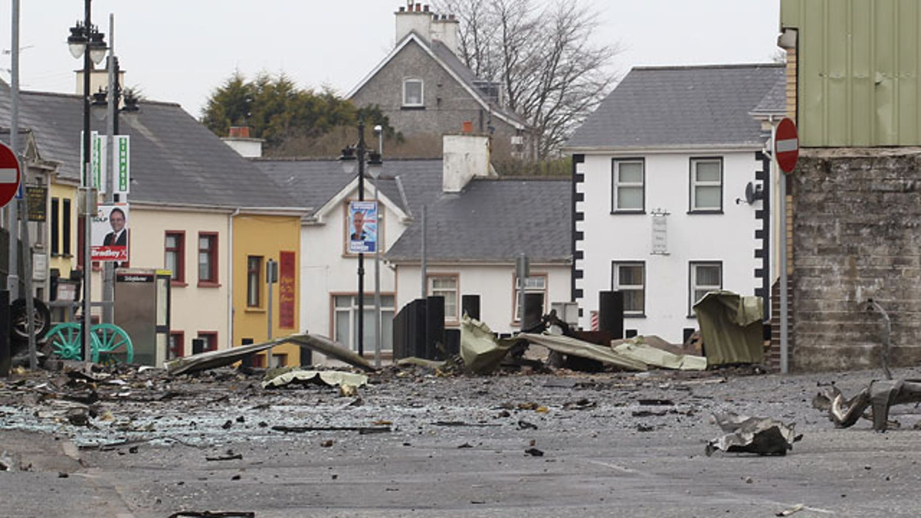 Wreckage lies across the street from car bomb outside Newtownhamilton Police Station, Northern Ireland, Friday, April, 23, 2010. Irish Republican Army dissidents fired gunshots and detonated a car bomb outside a security base in a Northern Ireland border village, injuring three people, police said Friday. The attack outside the heavily fortified Newtownhamilton police station is the third in the British territory this year by splinter IRA groups. They oppose Northern Ireland's peace process and the Catholic-Protestant government it forged.