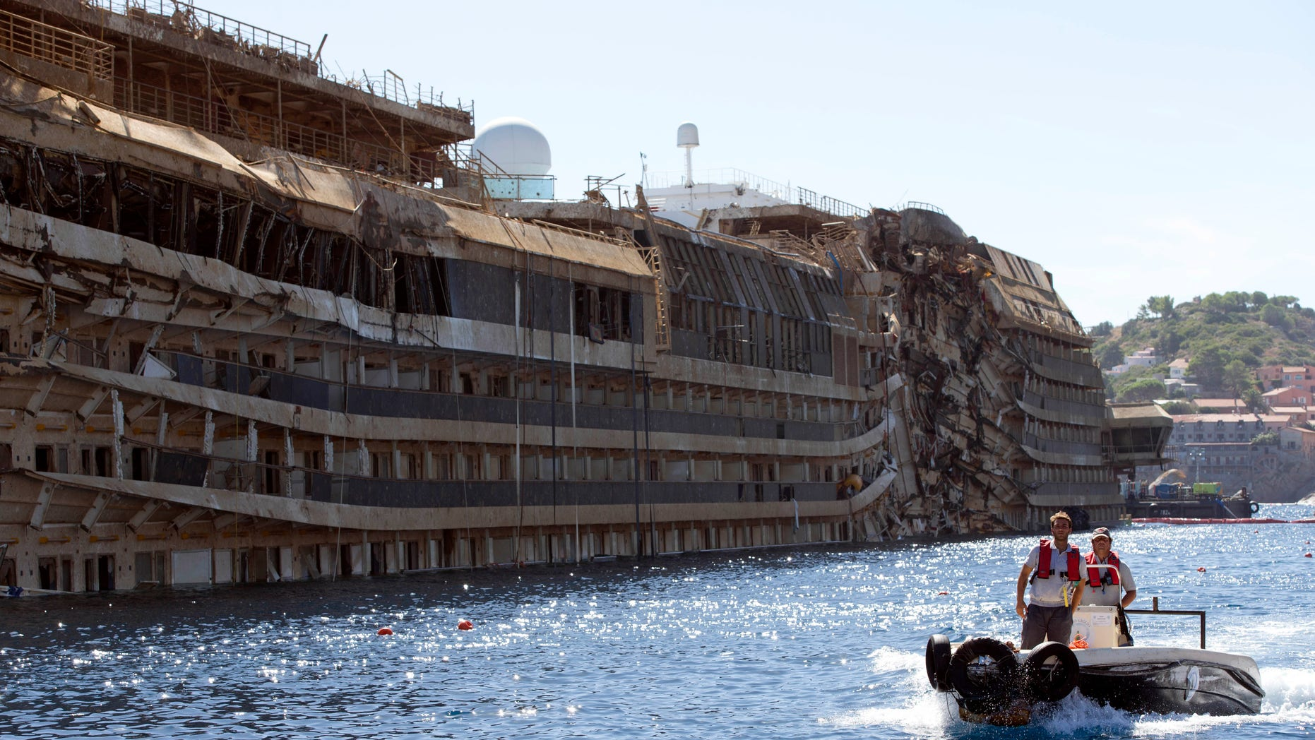 FILE - In this Sept. 18, 2013 file photo, a small boat navigates past the damaged side of the Costa Concordia ship after it was pulled upright, on the Tuscan Island of Giglio, Italy. Divers searching the submerged part of the wreck of the cruise ship have found the remains of one of the two people still missing from the 2012 disaster. Officials believe the remains belong to Russel Rebello, an Indian waiter. Thirty-two people died when the Concordia slammed into a reef off the Tuscan island of Giglio and capsized on Jan. 13, 2012. (AP Photo/Andrew Medichini, file)