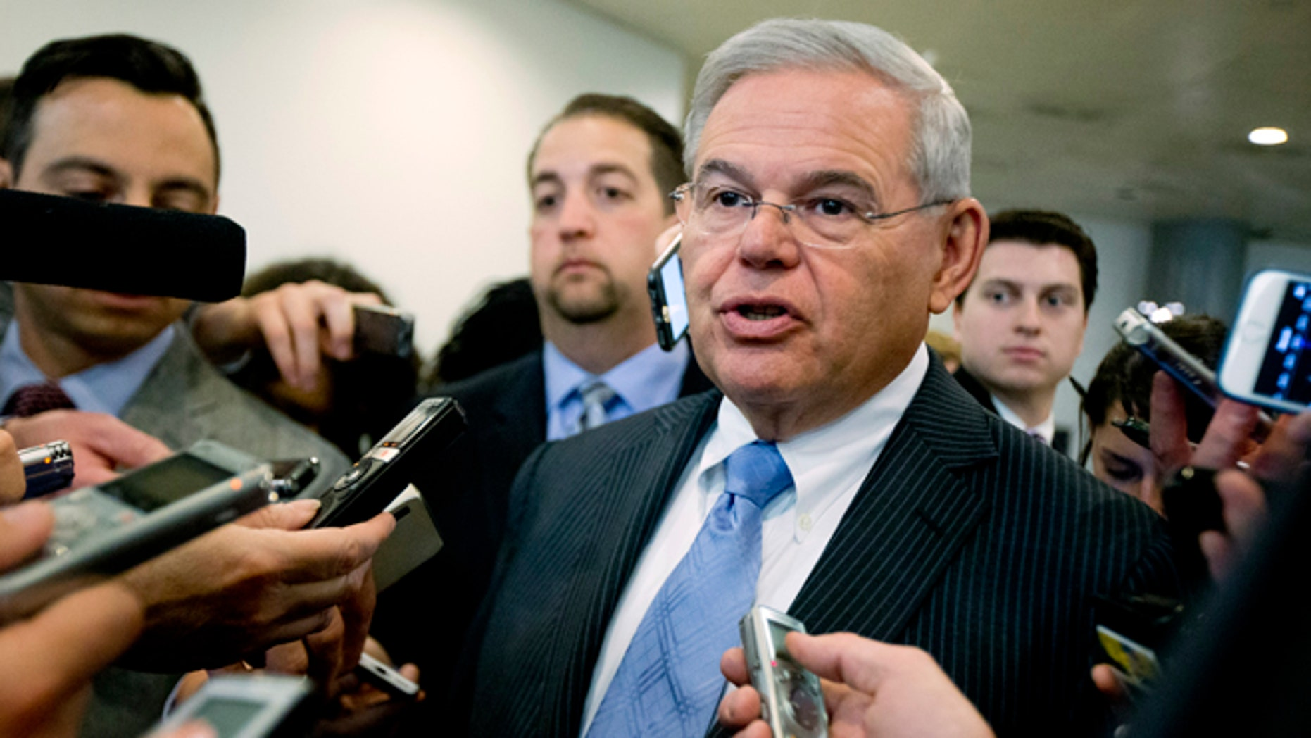 FILE - In this April 14, 2015, file photo, Sen.  Robert Menendez, D-N.J. speaks with members of the media on Capitol Hill in Washington. Menendez, facing a federal indictment on bribery and corruption charges, reported his legal defense fund has raised nearly $1.3 million since it was launched last year and $430,000 from the start of this year until the day before he was indicted. Menendez, a Democrat, has denied any wrongdoing and vowed to fight the indictment, which alleges he helped his longtime friend and co-defendant, Florida eye doctor Salomon Melgen, with his business dealings in exchange for trips to a lavish villa in the Dominican Republic and campaign donations. (AP Photo/Manuel Balce Ceneta, File)