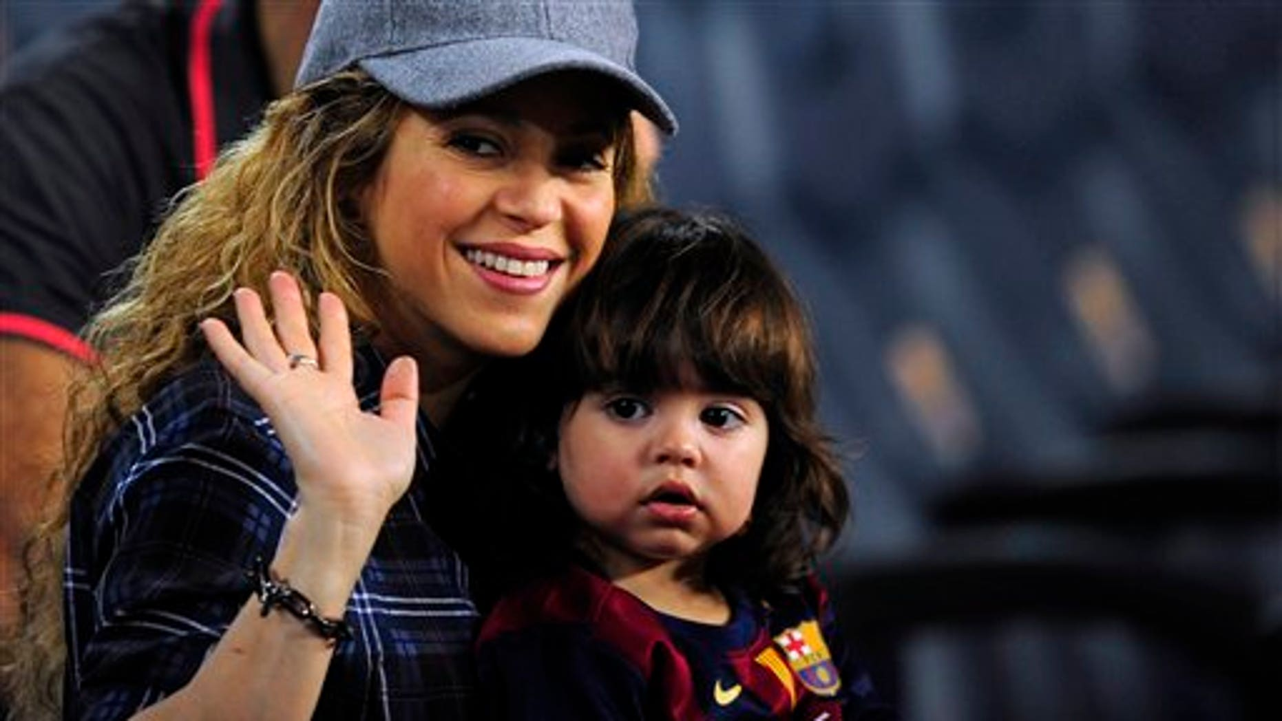 Colombian singer Shakira, left, waves with his son Milan prior of a Spanish La Liga soccer match between FC Barcelona and Eibar at the Camp Nou stadium against Eibar in Barcelona, Spain, Saturday, Oct. 18, 2014. (AP Photo/Manu Fernandez)
