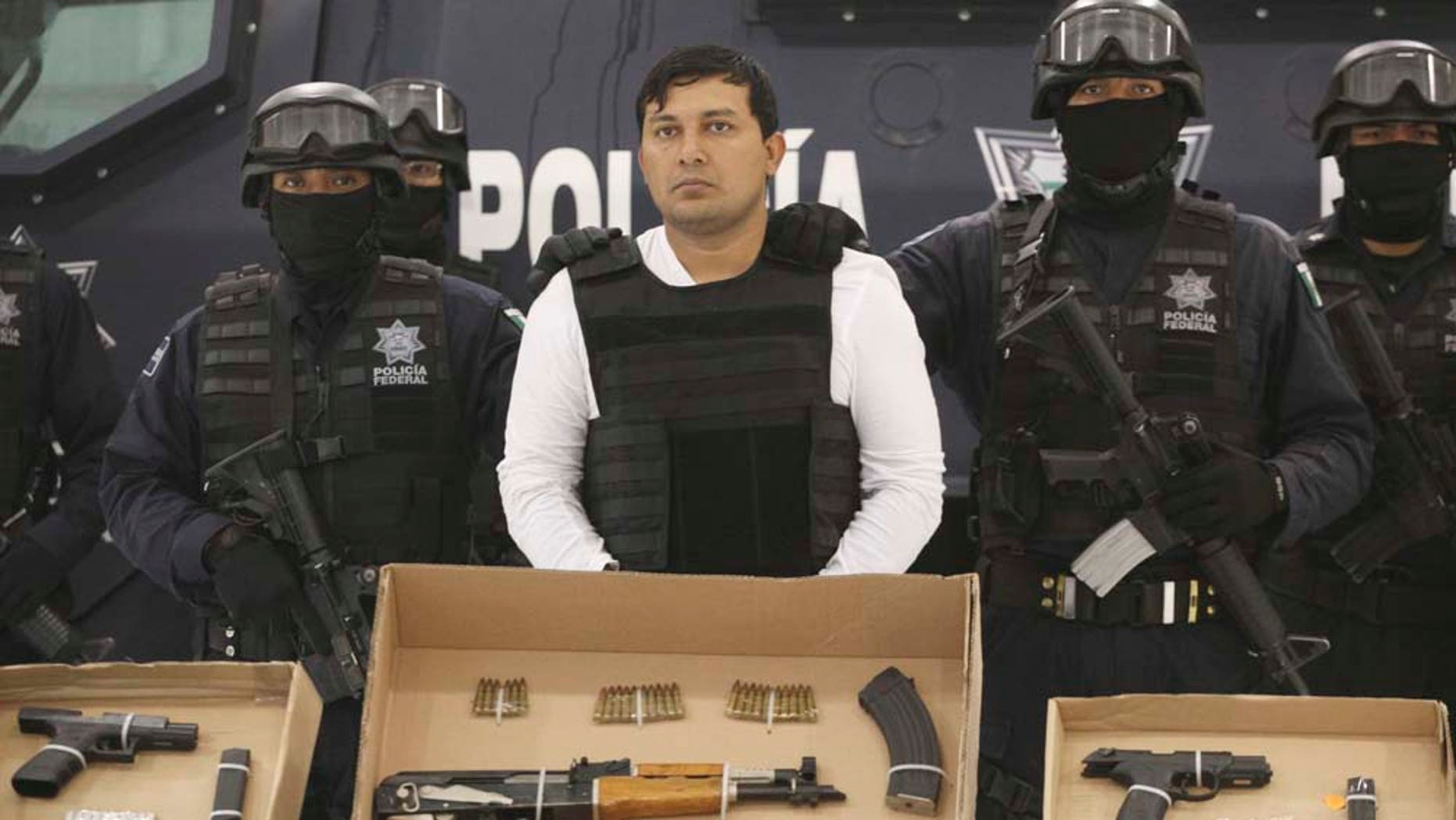 """Federal Police agents present Jesus Enrique Aguilar, alias """"El Mamito"""", center, to the media in Mexico City, Monday July 4, 2011. Police believe Aguilar is connected with the killing of a U.S. Immigration and Customs Enforcement agent. Aguilar is a former member of the Mexican Army and allegedly a co-founder of the Zetas drug cartel, according to authorities. (AP Photo/Alexandre Meneghini)"""