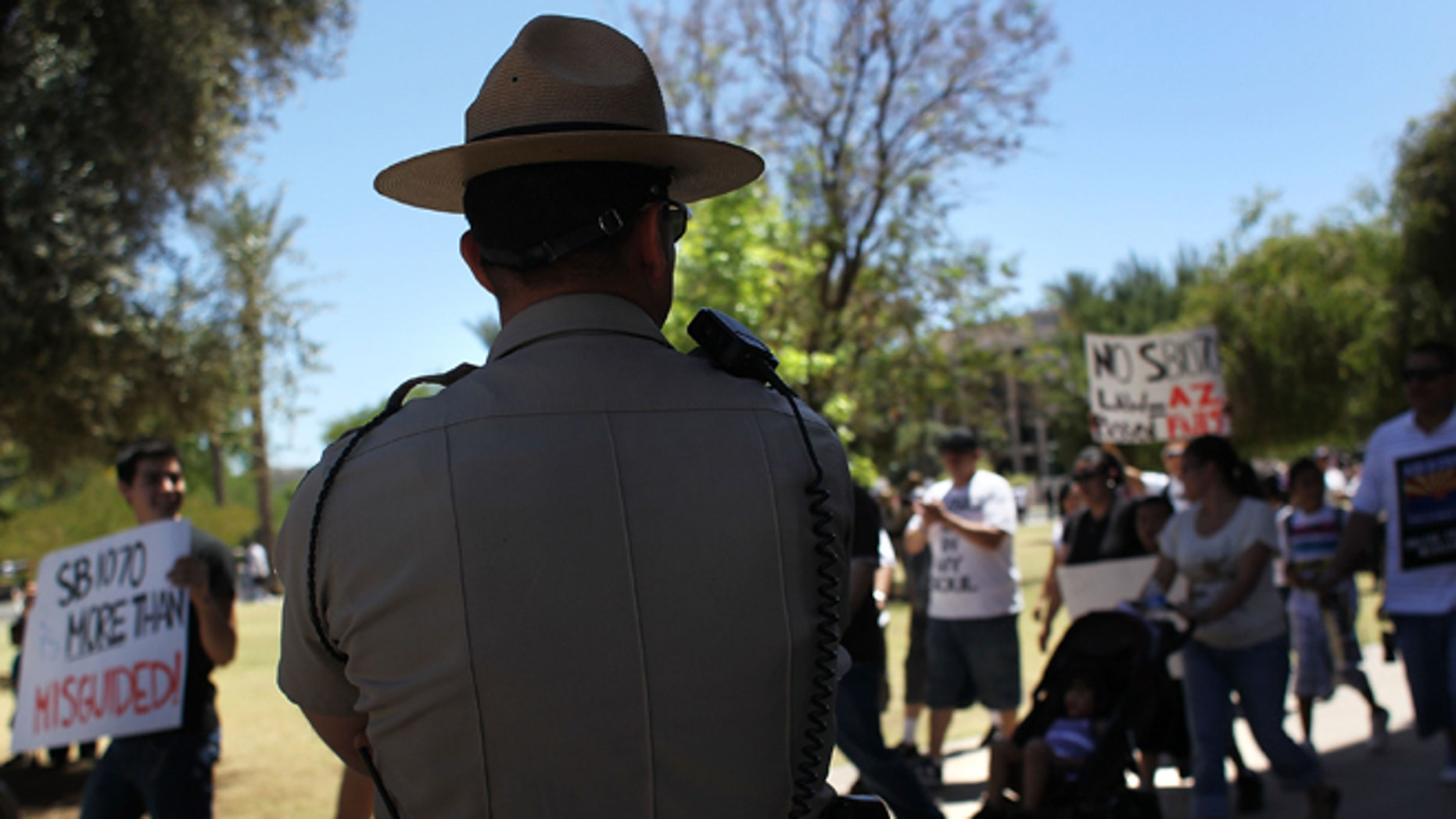PHOENIX - MAY 01:  A police officer watches demonstrators protest Arizona's new immigration enforcement law during a May Day rally at the state capitol building on May 1, 2010 in Phoenix, Arizona. Thousands of people in cities across the United States protested the immigration law, which critics have said could encourage racial profiling against Hispanics by police officers.  (Photo by John Moore/Getty Images)