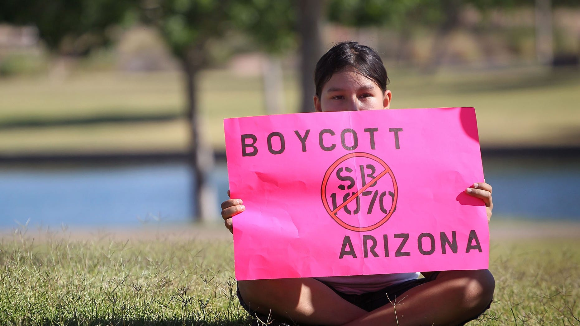 PHOENIX - MAY 29:  Litzy Medina waits waits to join a march through downtown to protest Arizona's controversial immigration law SB1070 on May 29, 2010 in Phoenix, Arizona. Organizers were predicting 50,000 people would participate in the march.  (Photo by Scott Olson/Getty Images)