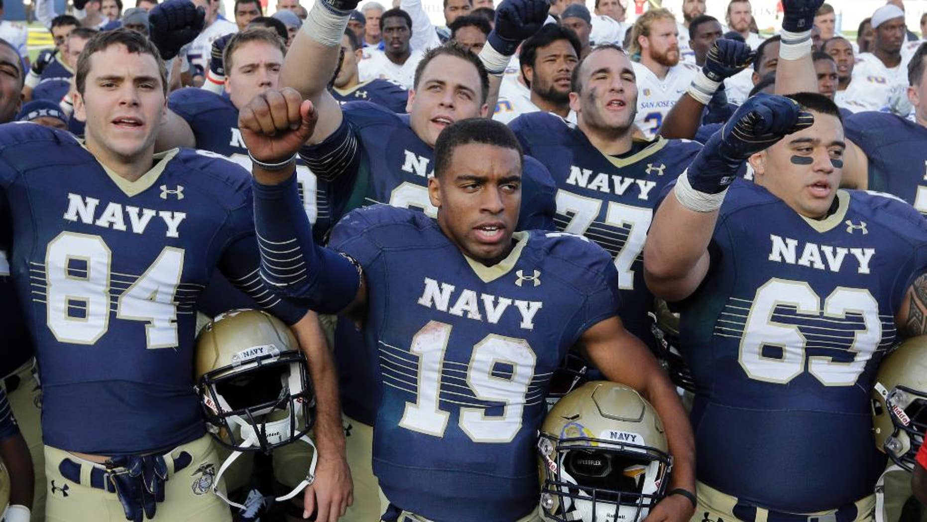 Navy quarterback Keenan Reynolds (19) sings the U.S. Naval Academy's alma mater alongside teammates after an NCAA college football game against San Jose State in Annapolis, Md., Saturday, Oct. 25, 2014. Navy won 41-31. (AP Photo/Patrick Semansky)