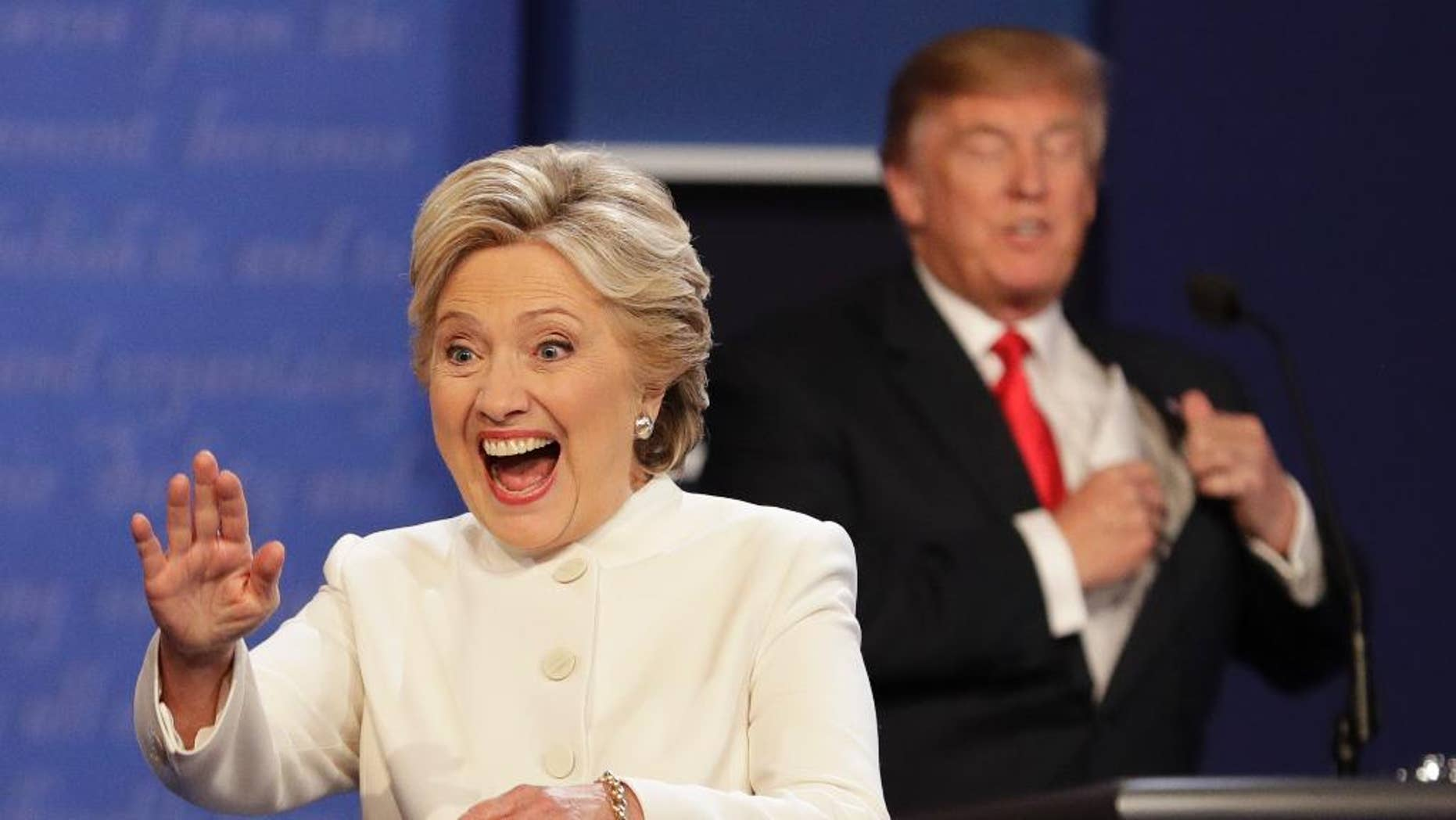 Democratic presidential nominee Hillary Clinton waves to the audience as Republican presidential nominee Donald Trump puts his notes away after the third presidential debate at UNLV in Las Vegas, Wednesday, Oct. 19, 2016. (AP Photo/John Locher)