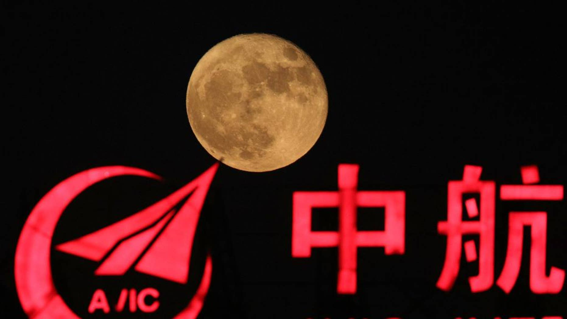 FILE - in This Tuesday, Nov. 15, 2016, file photo, the moon rises over a logo for AVIC or Aviation Industry Corp in Beijing, China. China is talking with the European Space Agency about collaborating on a human outpost on the moon. The chief engineer for China's space agency disclosed the talks Wednesday in Chinese state media. (AP Photo/Ng Han Guan, File )