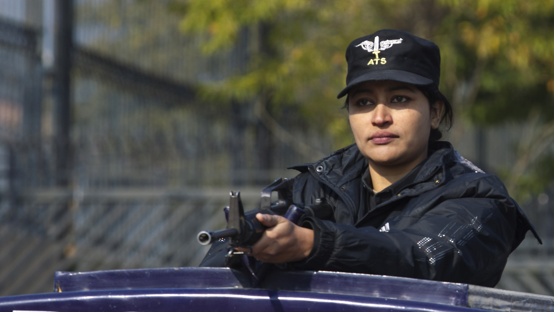 A Pakistani female police officer stands alert outside a court set up for the trial of Pakistan's former president and military ruler Pervez Musharraf in Islamabad, Pakistan, Wednesday, Jan. 1, 2014. Musharraf failed to appear in court Wednesday for the second hearing in his high-profile treason case after authorities said they found an explosive device near his home. (AP Photo/B.K. Bangash)