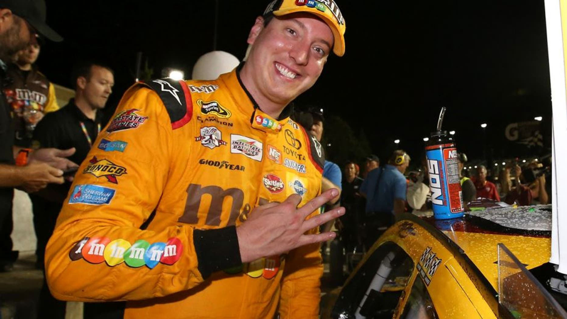 KANSAS CITY, KS - MAY 07: Kyle Busch, driver of the #18 M&M's Red Nose Toyota, celebrates after winning the NASCAR Sprint Cup Series Go Bowling 400 at Kansas Speedway on May 7, 2016 in Kansas City, Kansas. (Photo by Sean Gardner/NASCAR via Getty Images)